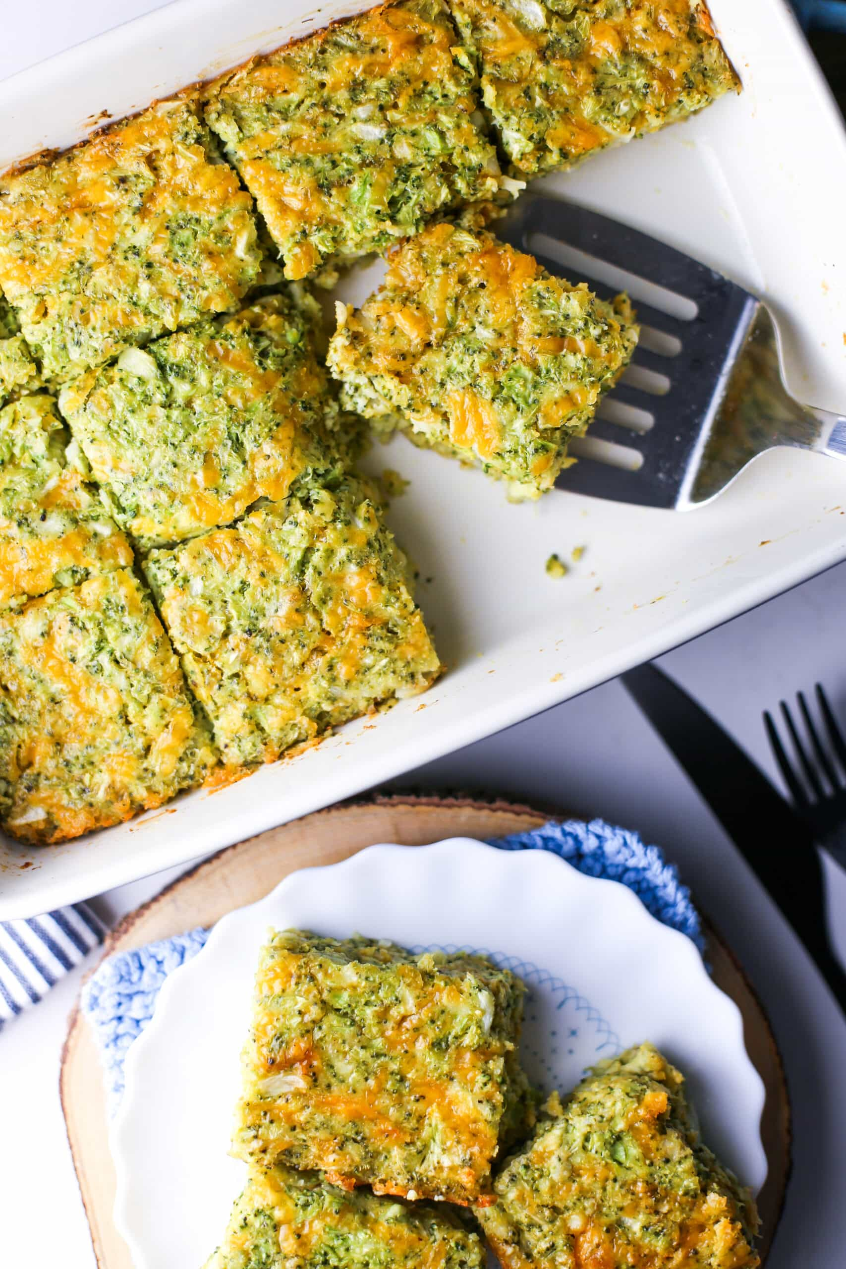 Overhead view of broccoli cheddar squares on a rectangular baking dish and white plate.