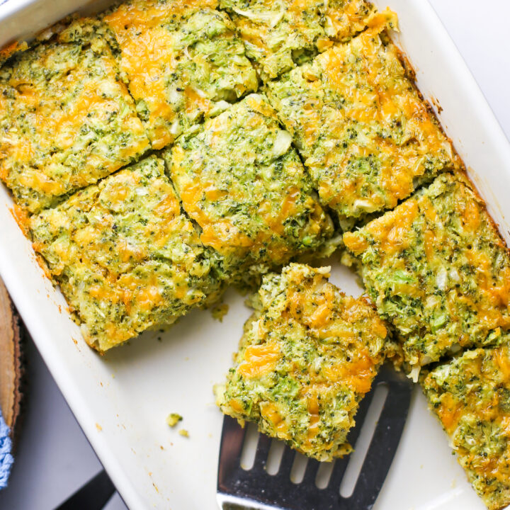 Overhead view of broccoli cheddar squares on a rectangular baking dish with a metal spatula.