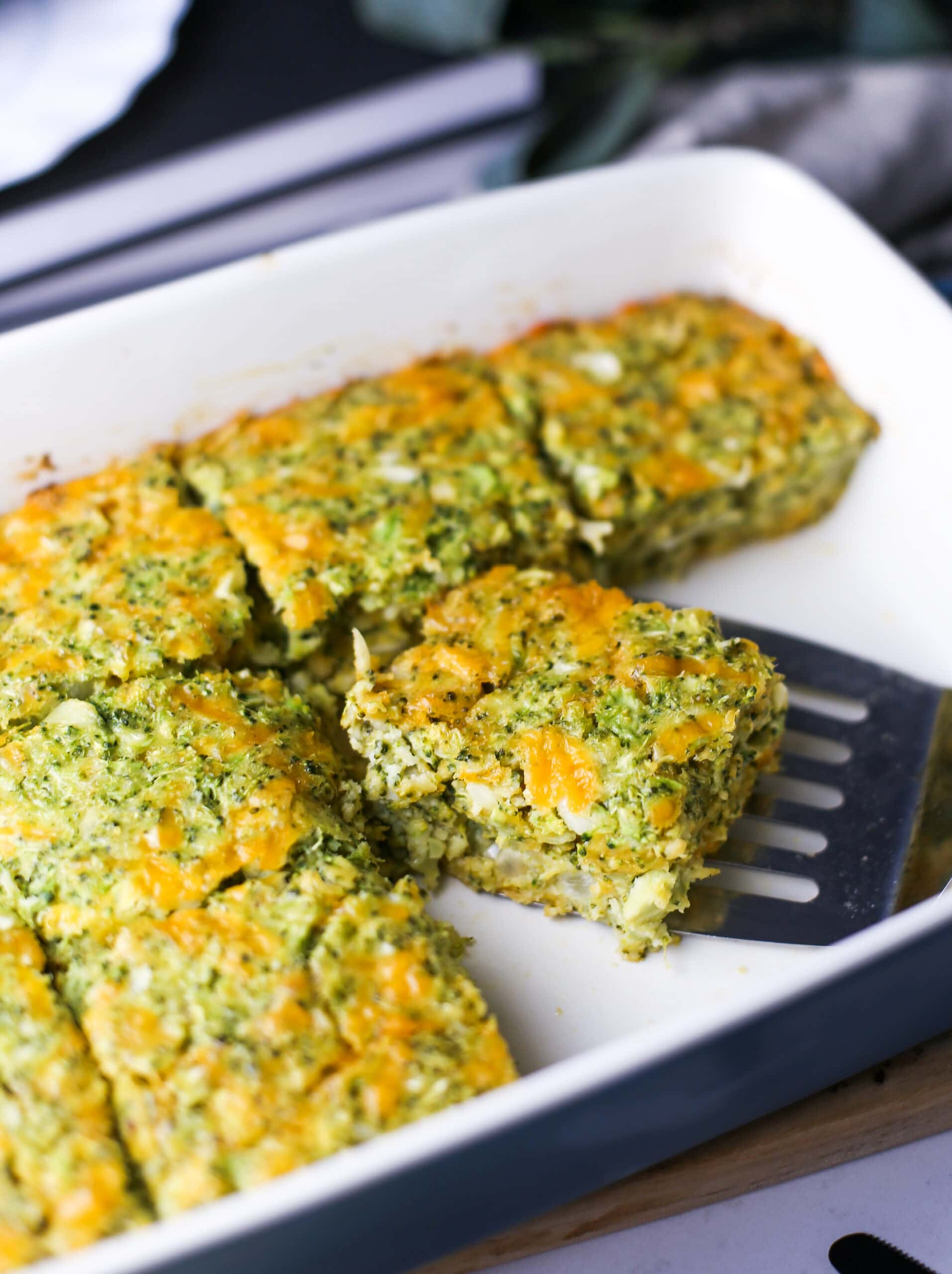A top angled view of broccoli cheddar squares in a baking dish.