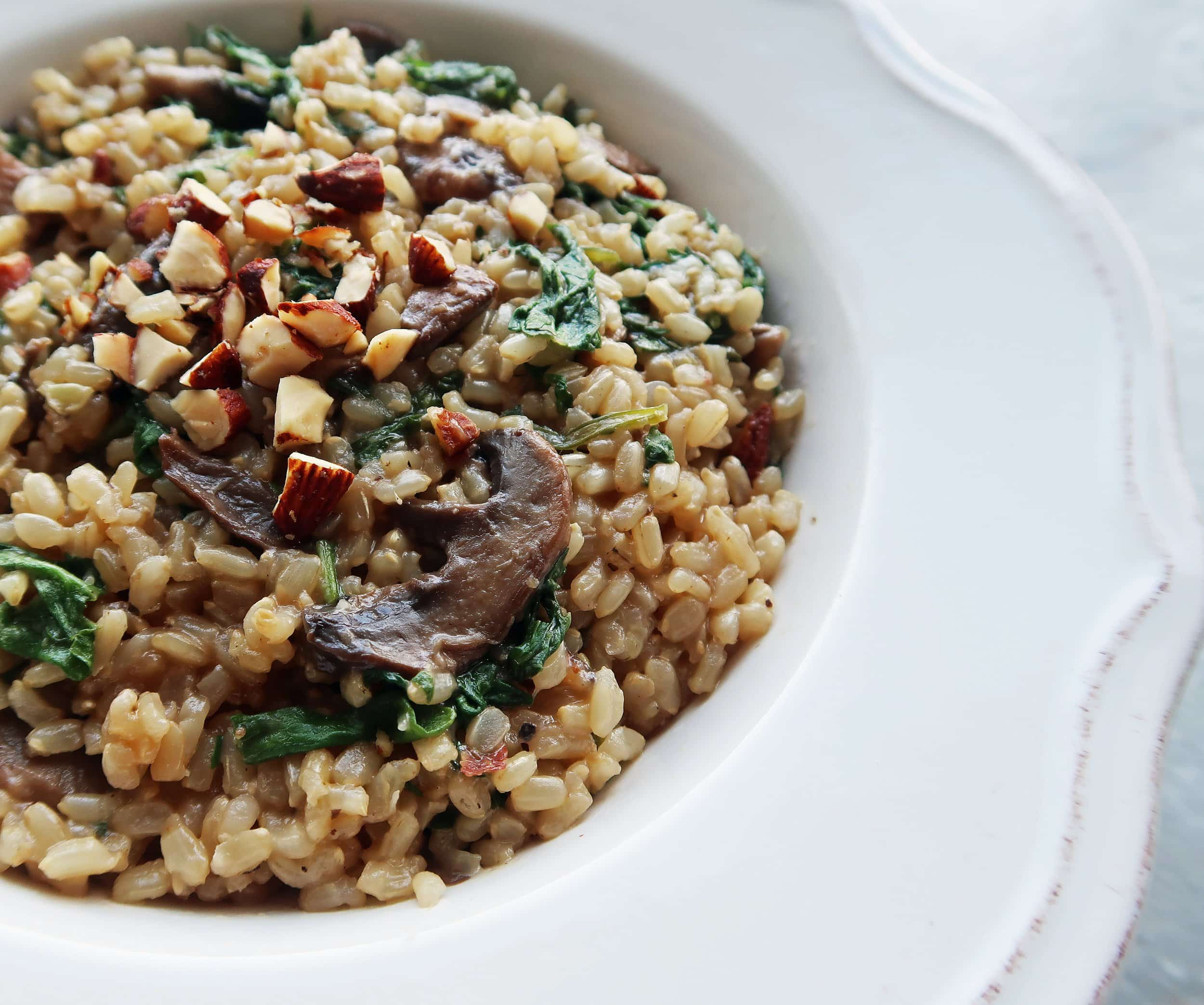A close up of a bowl of Brown Rice Pilaf with Mushrooms, Kale, and Almonds
