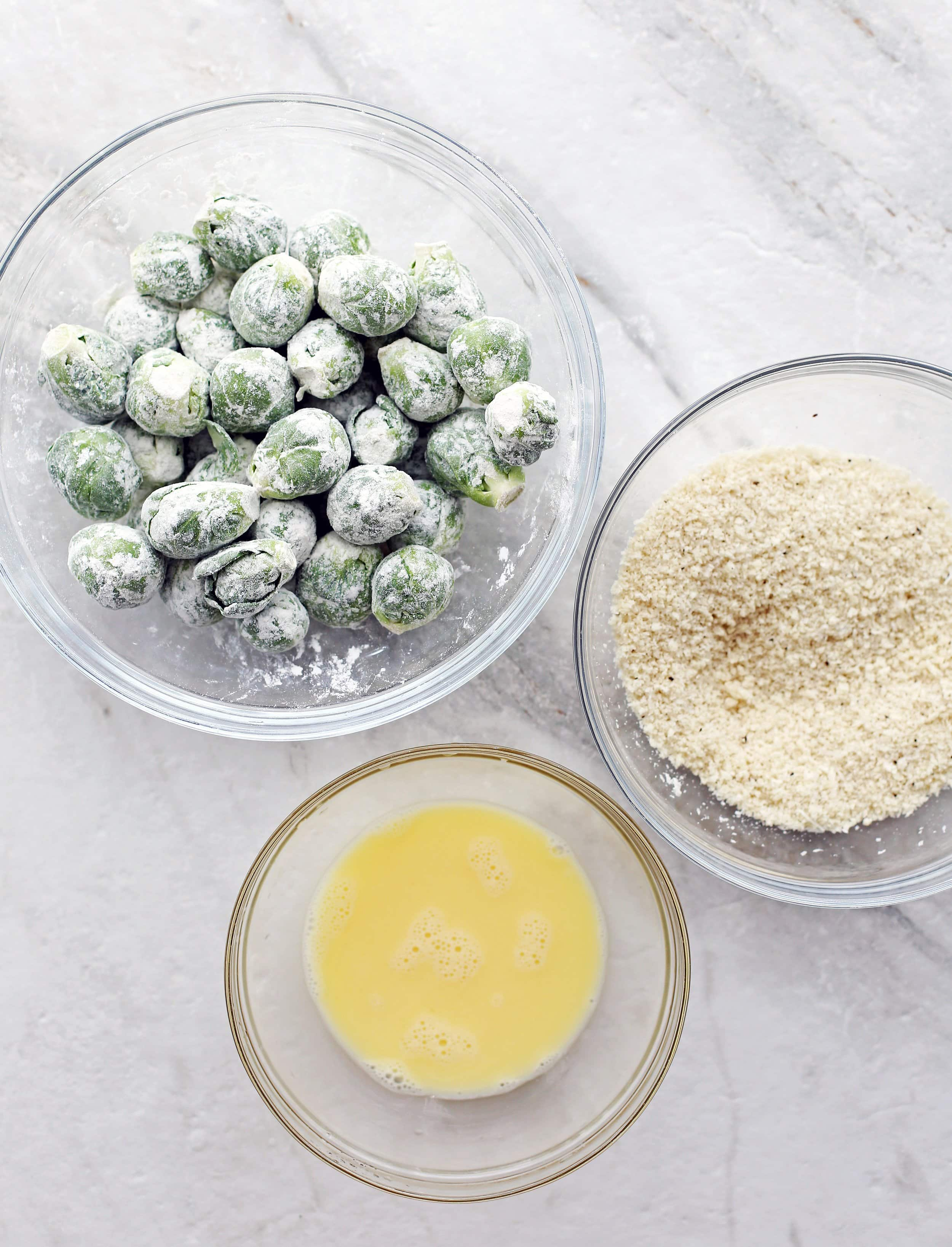 Bowls containing beaten eggs, breadcrumbs, and floured Brussels sprouts.