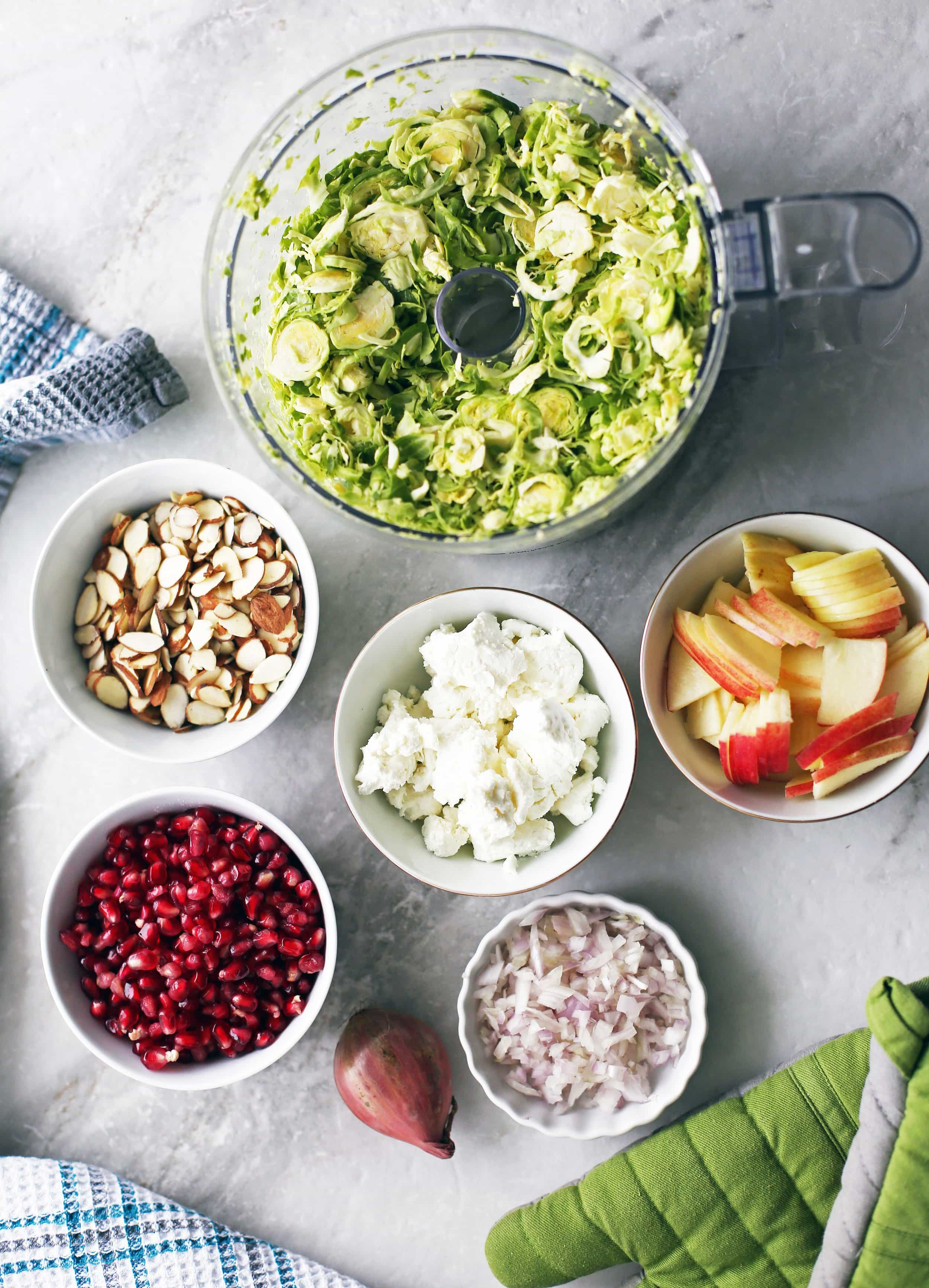 An overhead view of a bowls of shaved Brussels sprouts, almonds, pomegranate arils, shallot, goat cheese, and apple.