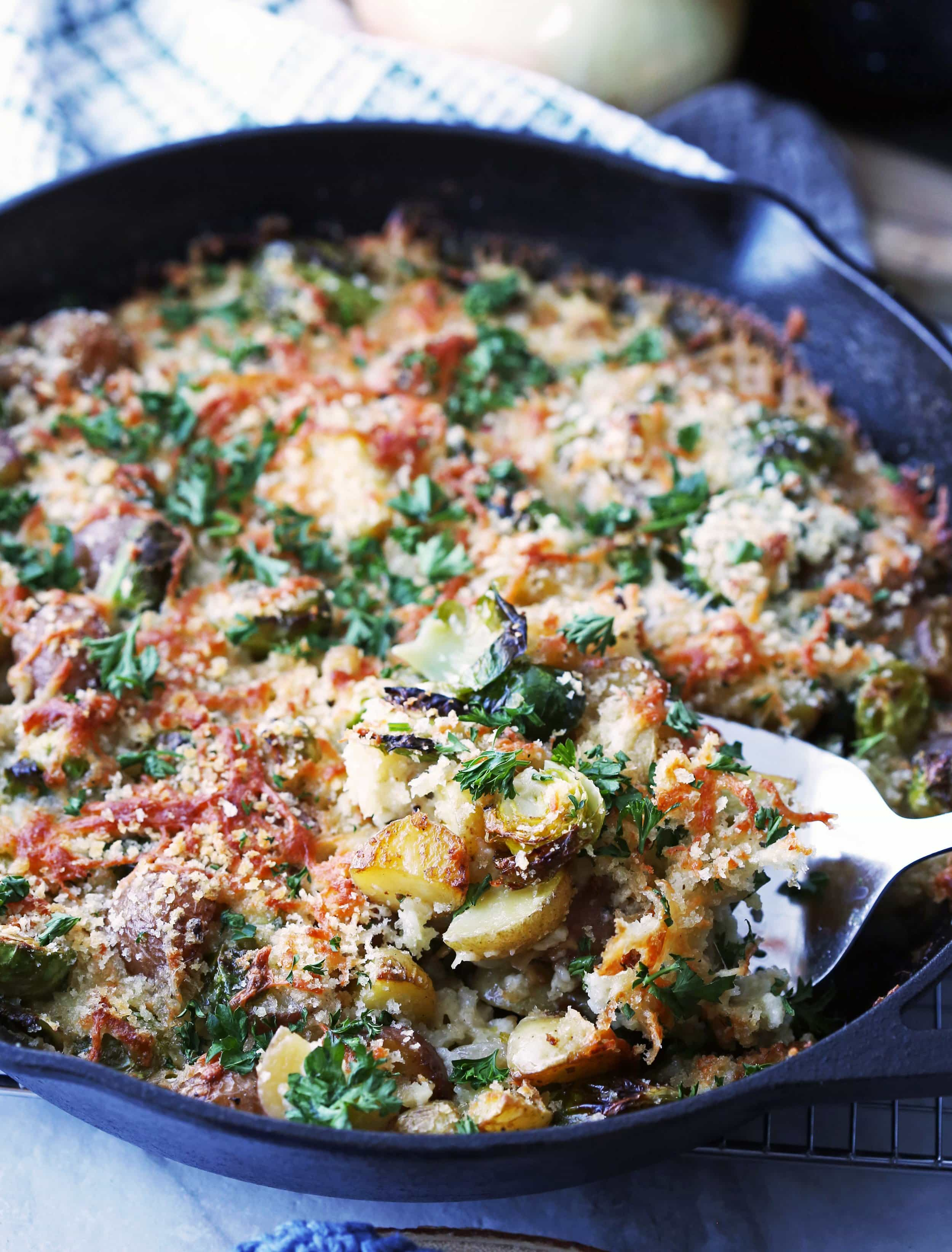 Baked Brussels Sprouts and Potato Gratin topped with crispy melted cheese, breadcrumbs, and parsley in a large cast iron skillet.