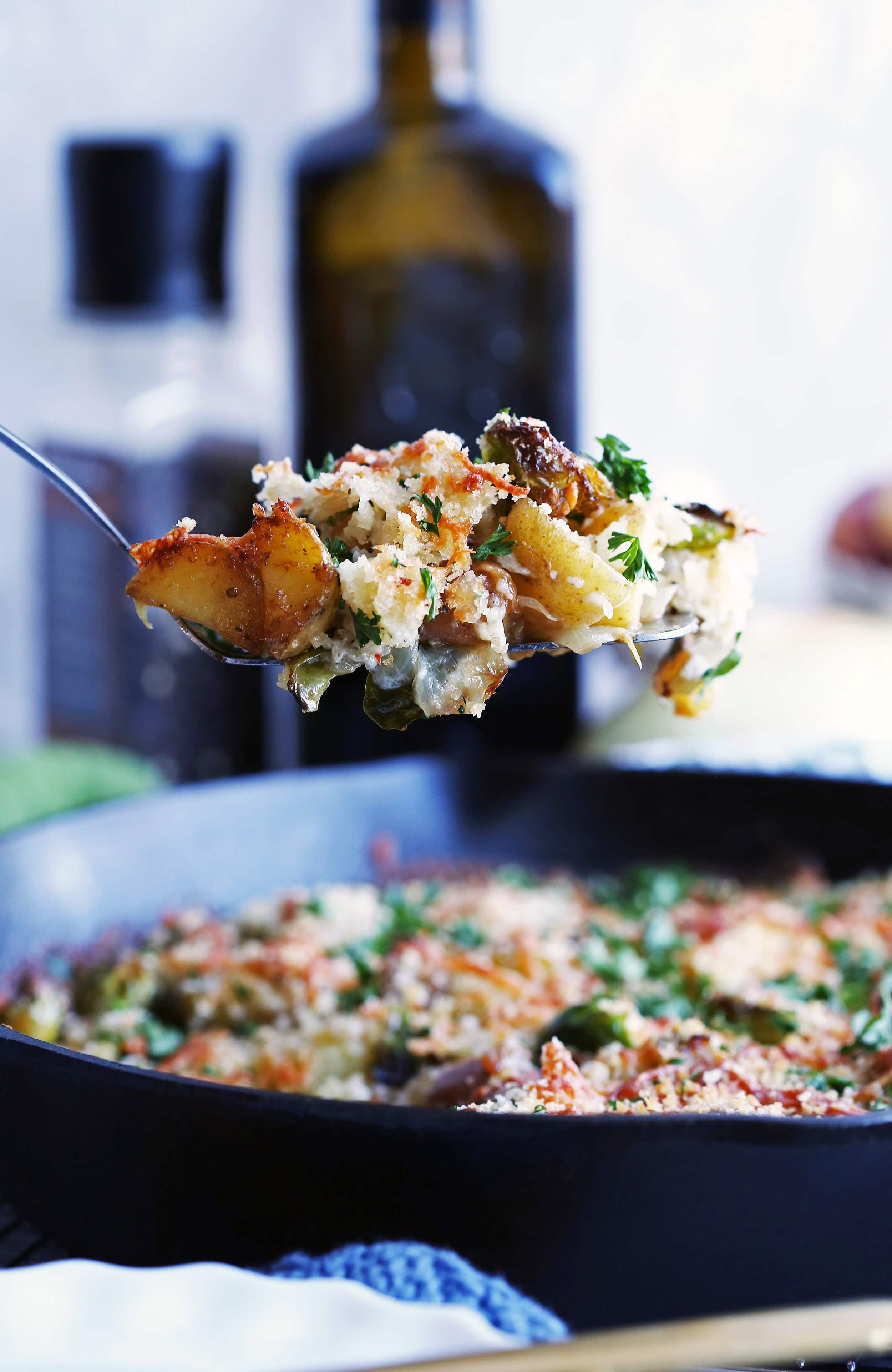 A heaping scoop of Brussels Sprouts and Potato Gratin on a metal spatula held over a large cast iron skillet with more gratin in it.