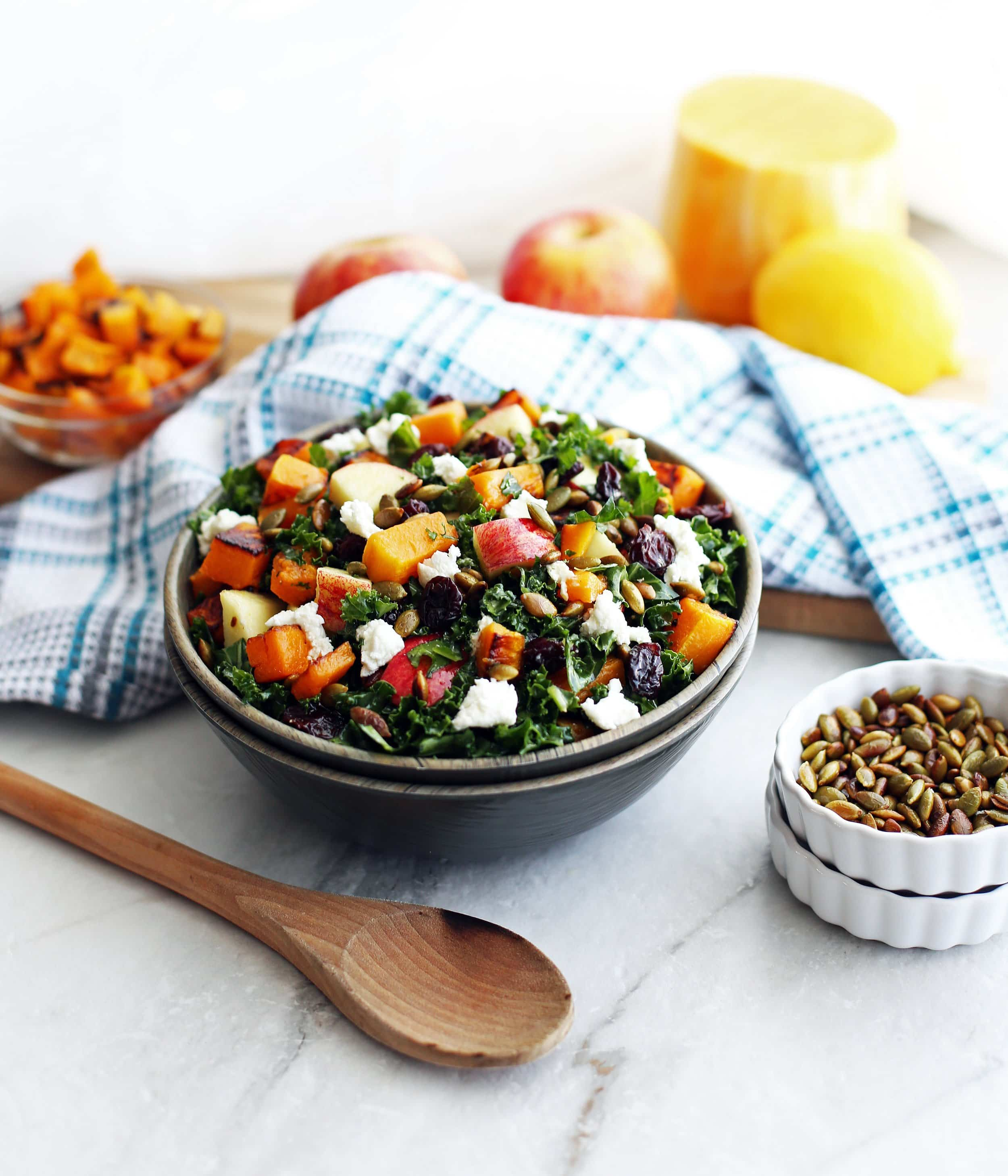A wooden bowl filled with Roasted Butternut Squash and Apple Kale Salad with Lemon Vinaigrette