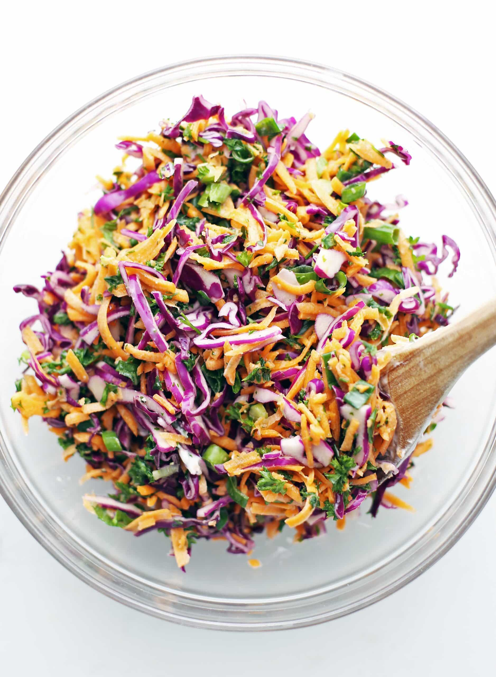 A glass bowl containing colourful and healthy carrot cabbage coleslaw.