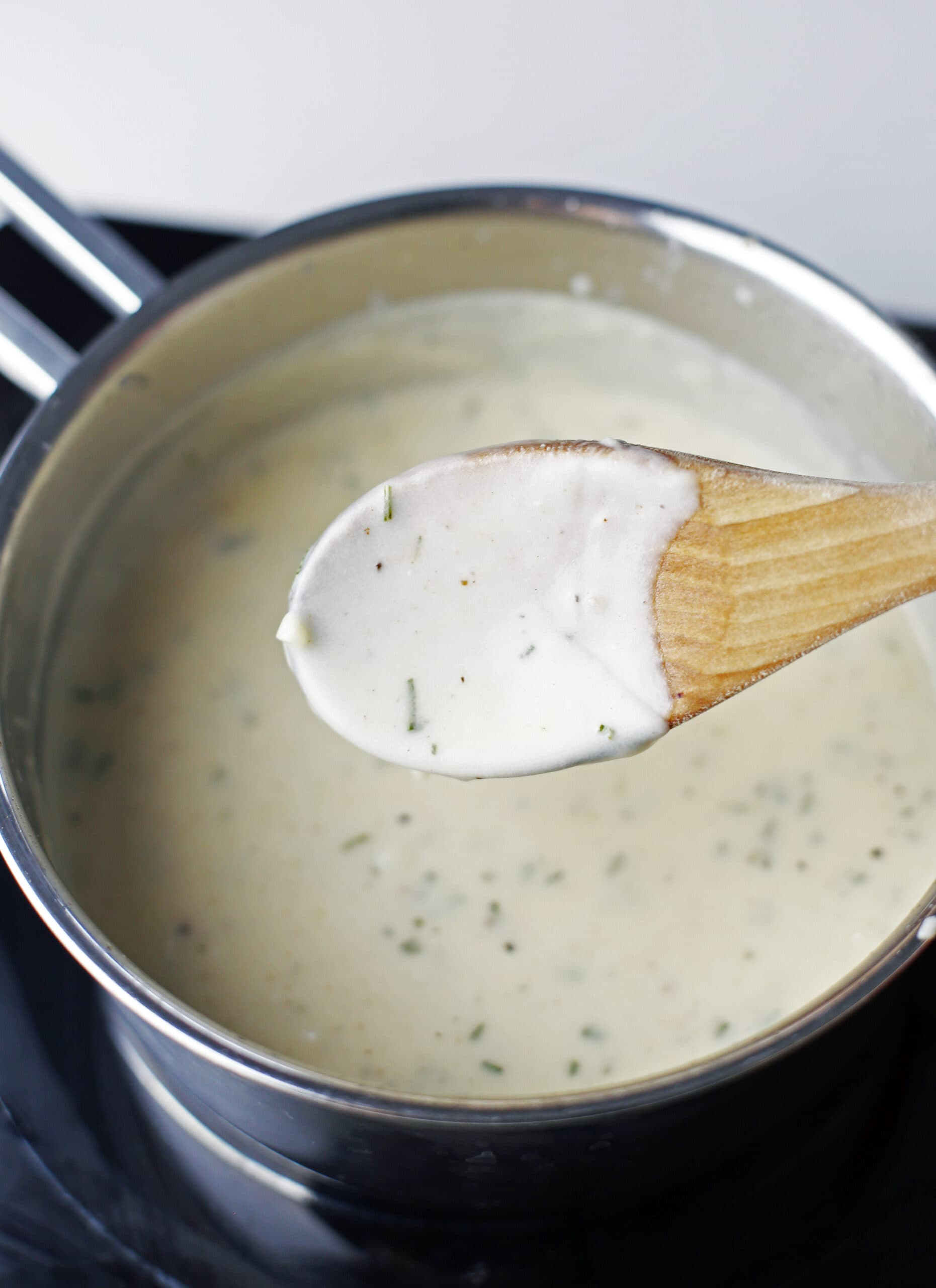 A wooden spoon with a coat of cheese sauce over saucepan of the same sauce.