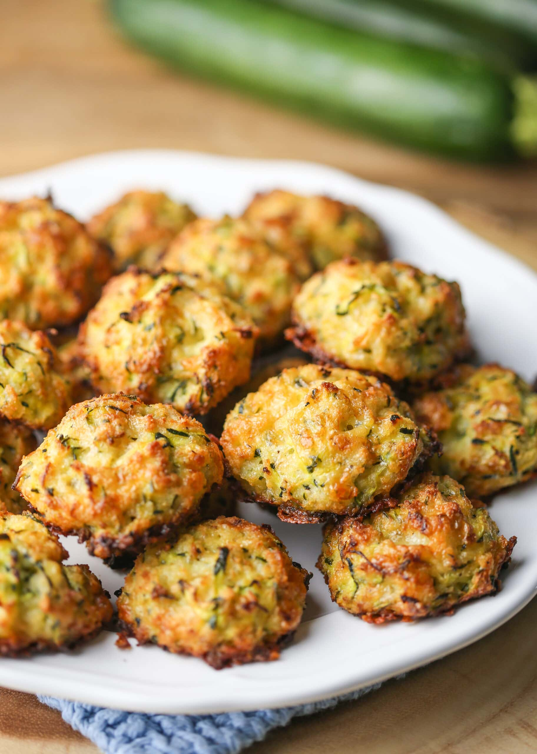 Golden-brown cheesy baked zucchini bites on a white plate.