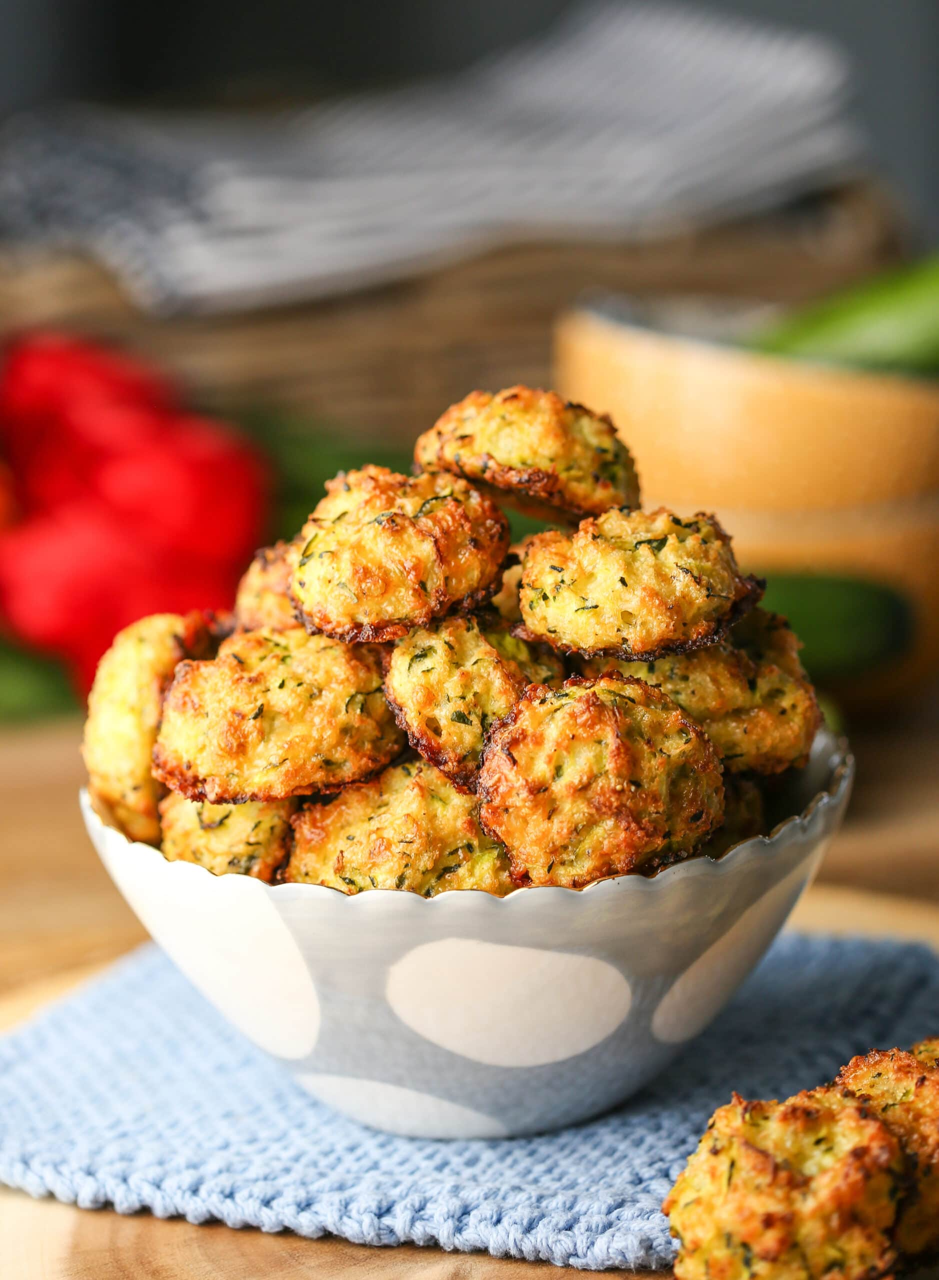 Golden-brown baked cheesy zucchini bites in a white and blue bowl.