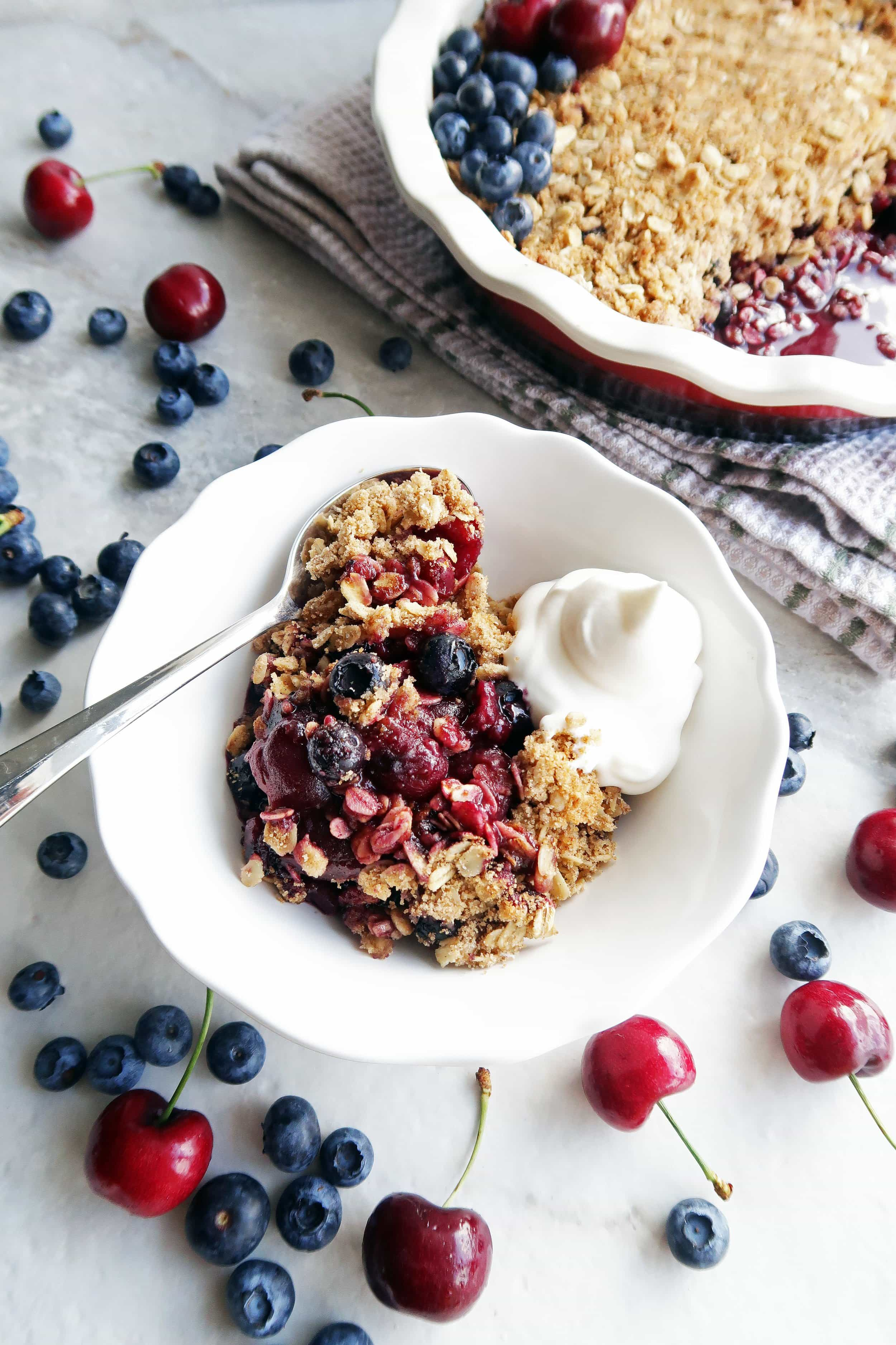 Cherry blueberry oat crisp with cream in a white bowl with a spoon and a pie dish of oat crisp in the background.