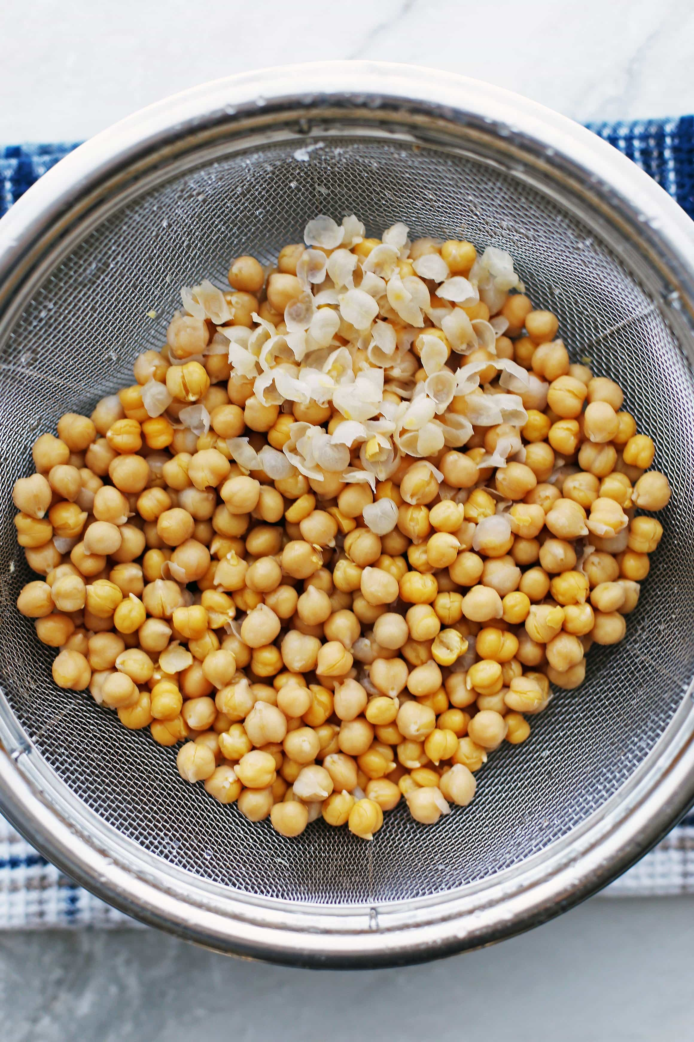 Rinsed and drained cooked chickpeas in a wire strainer.