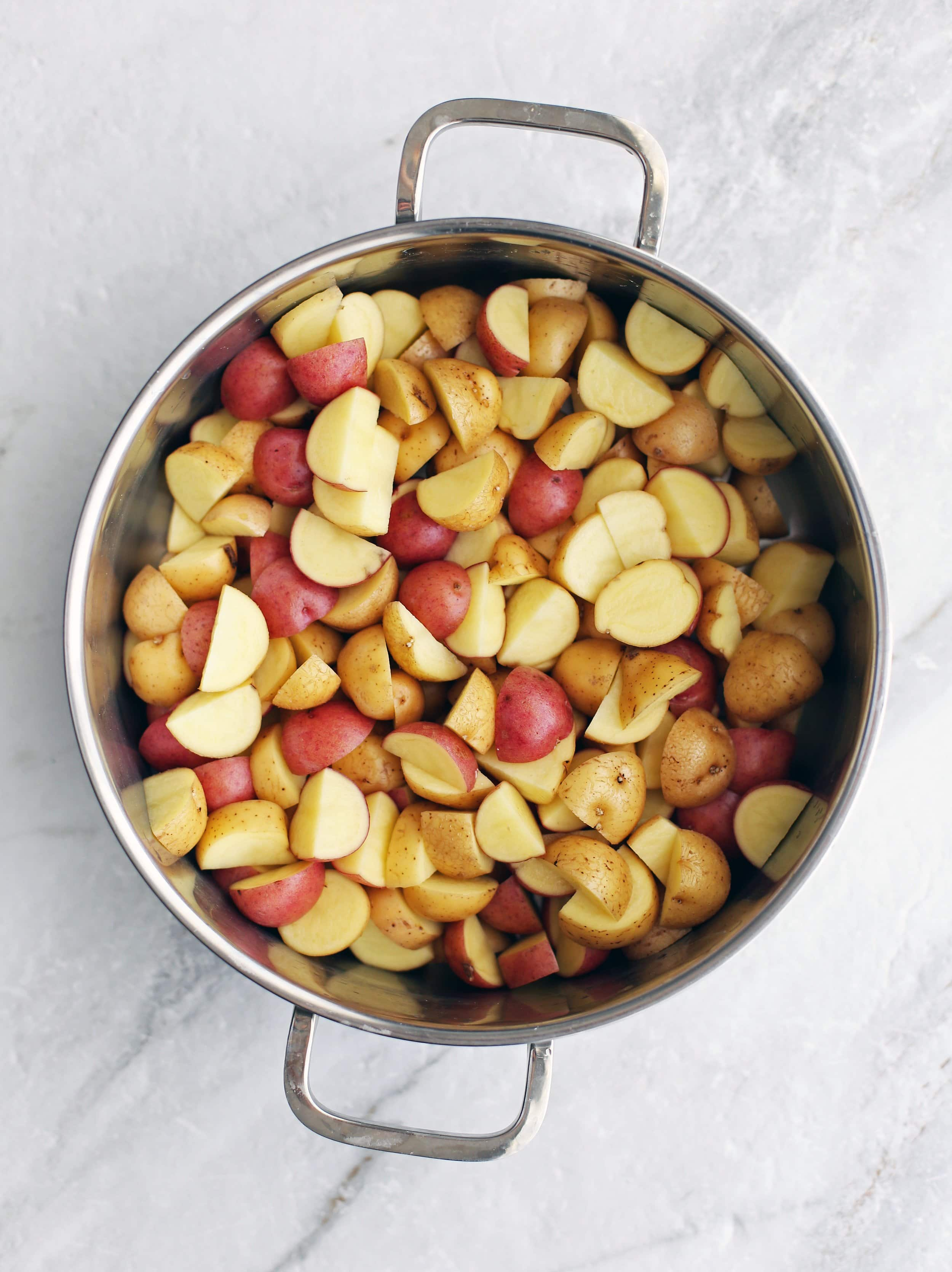 Quartered red and yellow baby potatoes in a large metal pot.