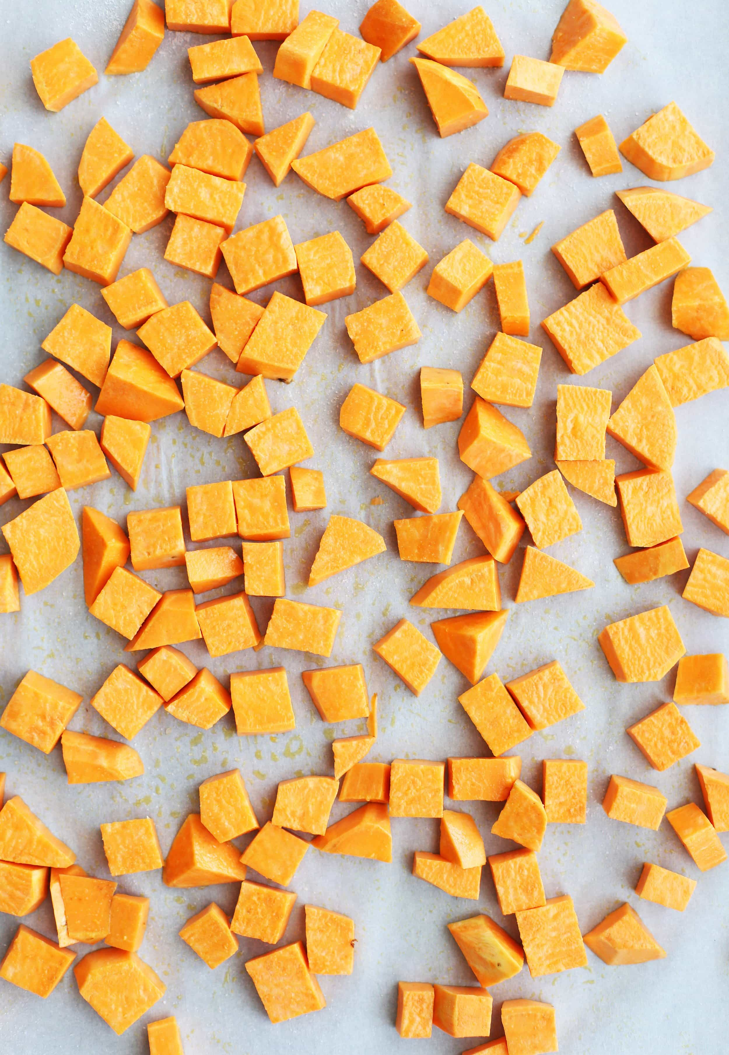 Peeled and chopped sweet potatoes on a baking sheet lined with parchment paper.