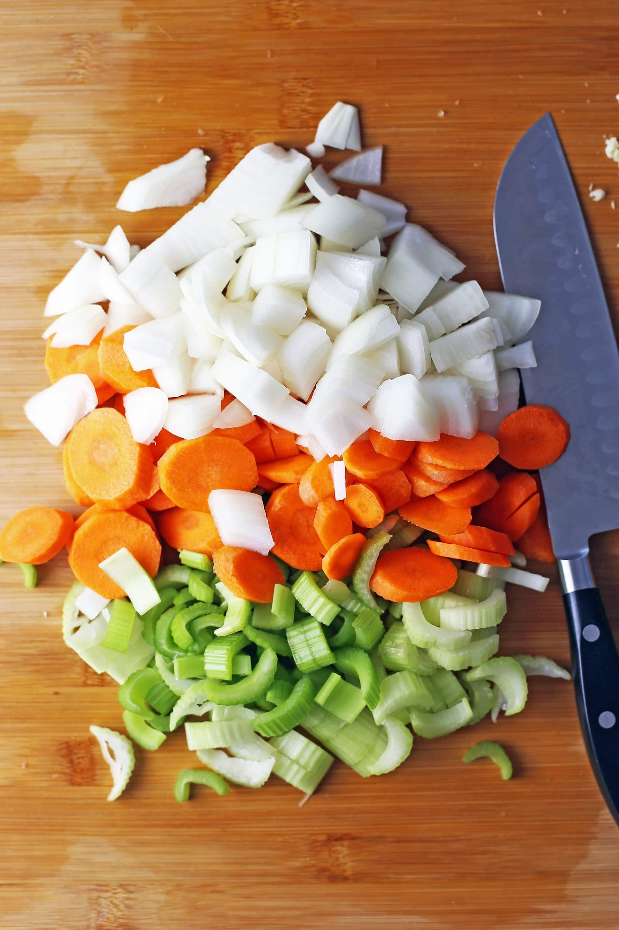 Chopped white onion, carrots, and celery on wooden cutting board with a knife on the the side of the vegetables.
