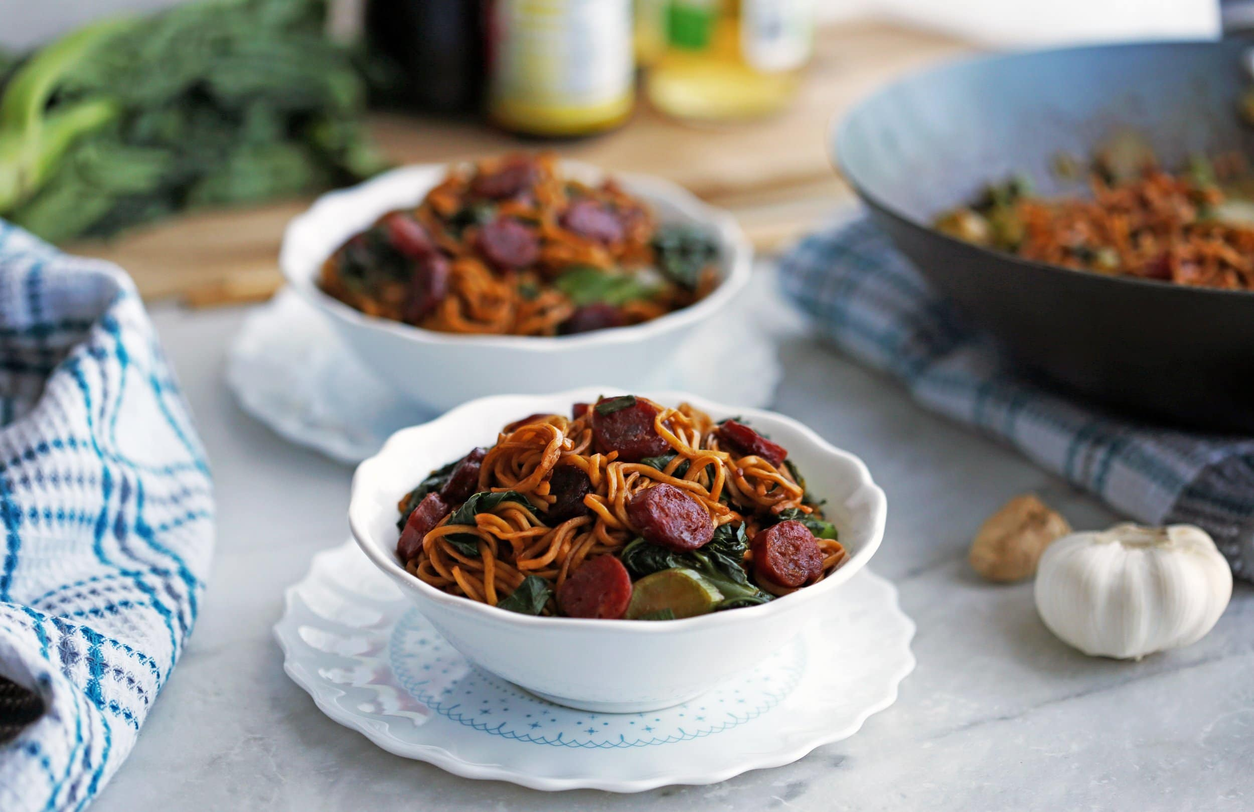 Two bowls of Lo mein noodles with Chinese sausage (lap cheong) and gai lan (Chinese broccoli).