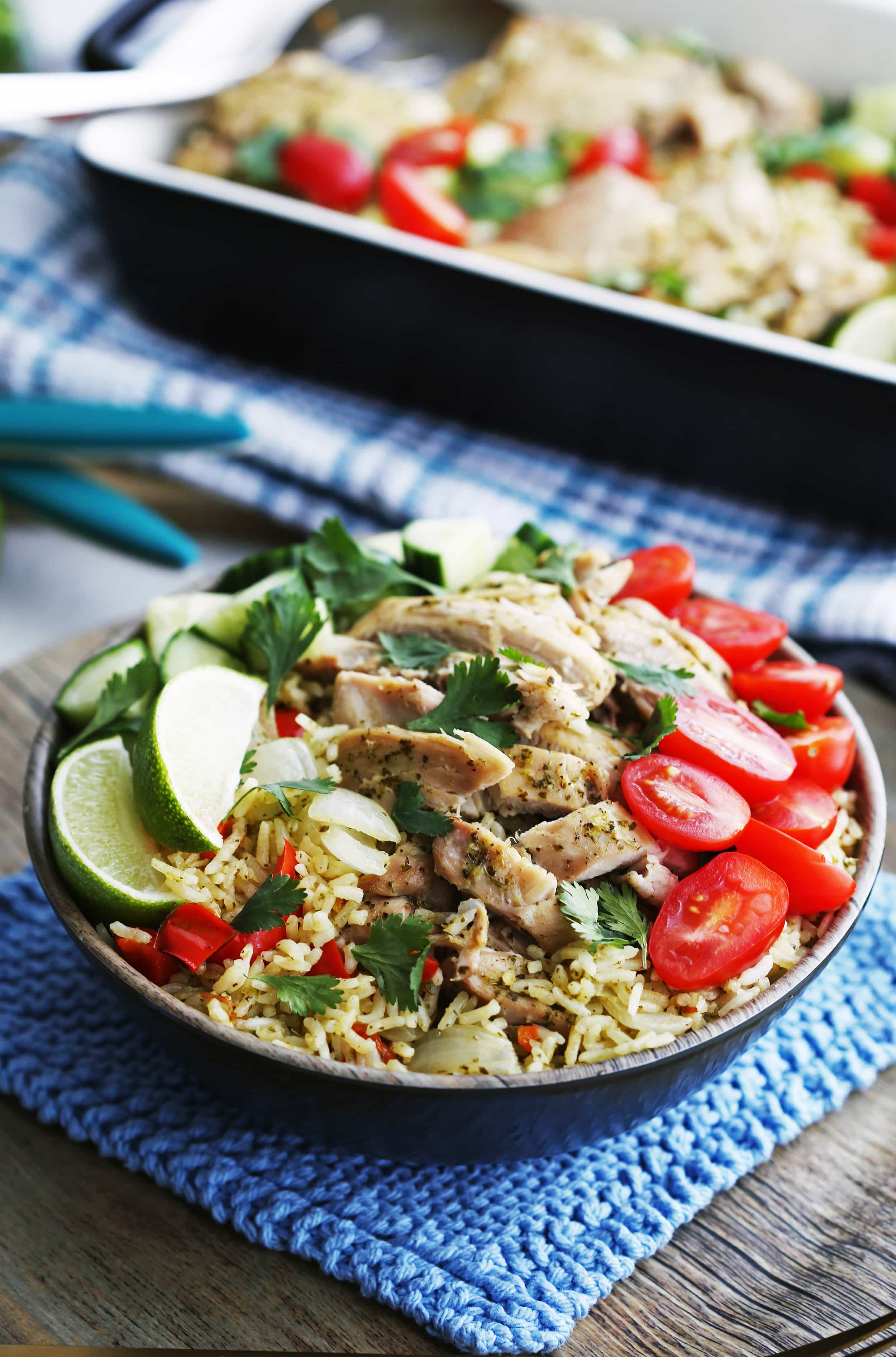 A full bowl of Instant Pot Cilantro Lime Chicken and Rice with fresh tomatoes, cilantro, cucumber, and lime wedges.