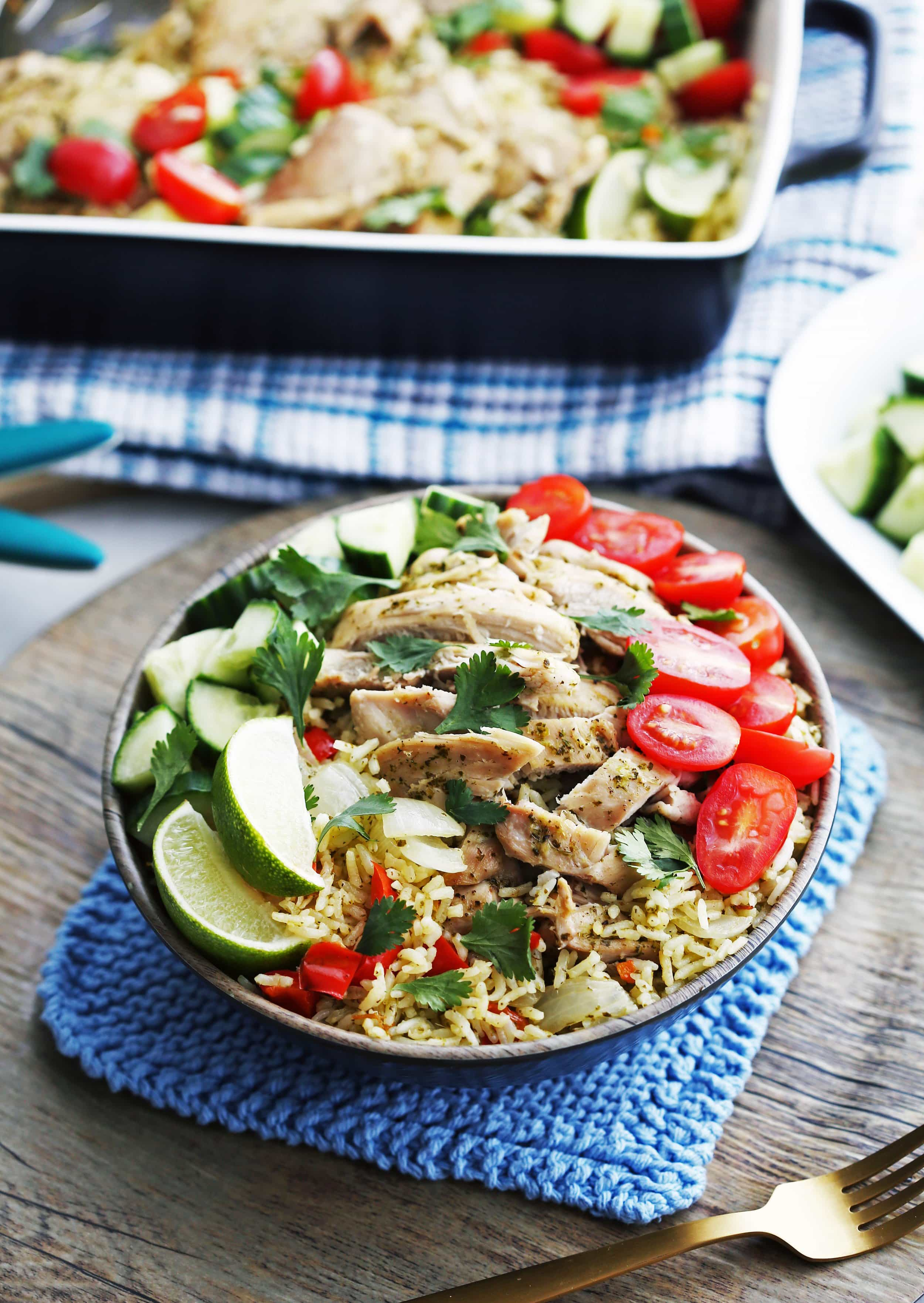 Cilantro Lime Chicken and Rice with tomatoes, cucumbers, cilantro, and lime wedges in a wooden bowl.