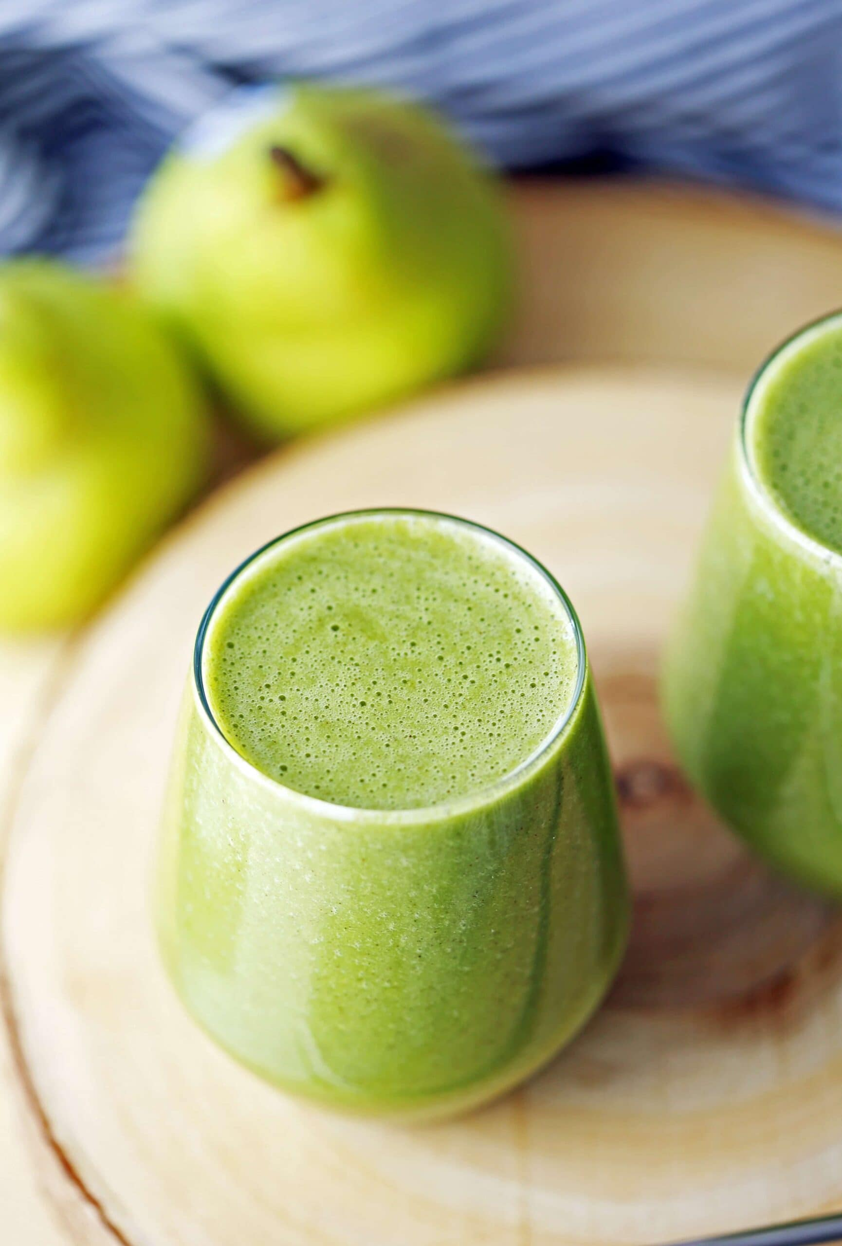 A top angled view of a glass filled with cinnamon pear green smoothie with spinach.