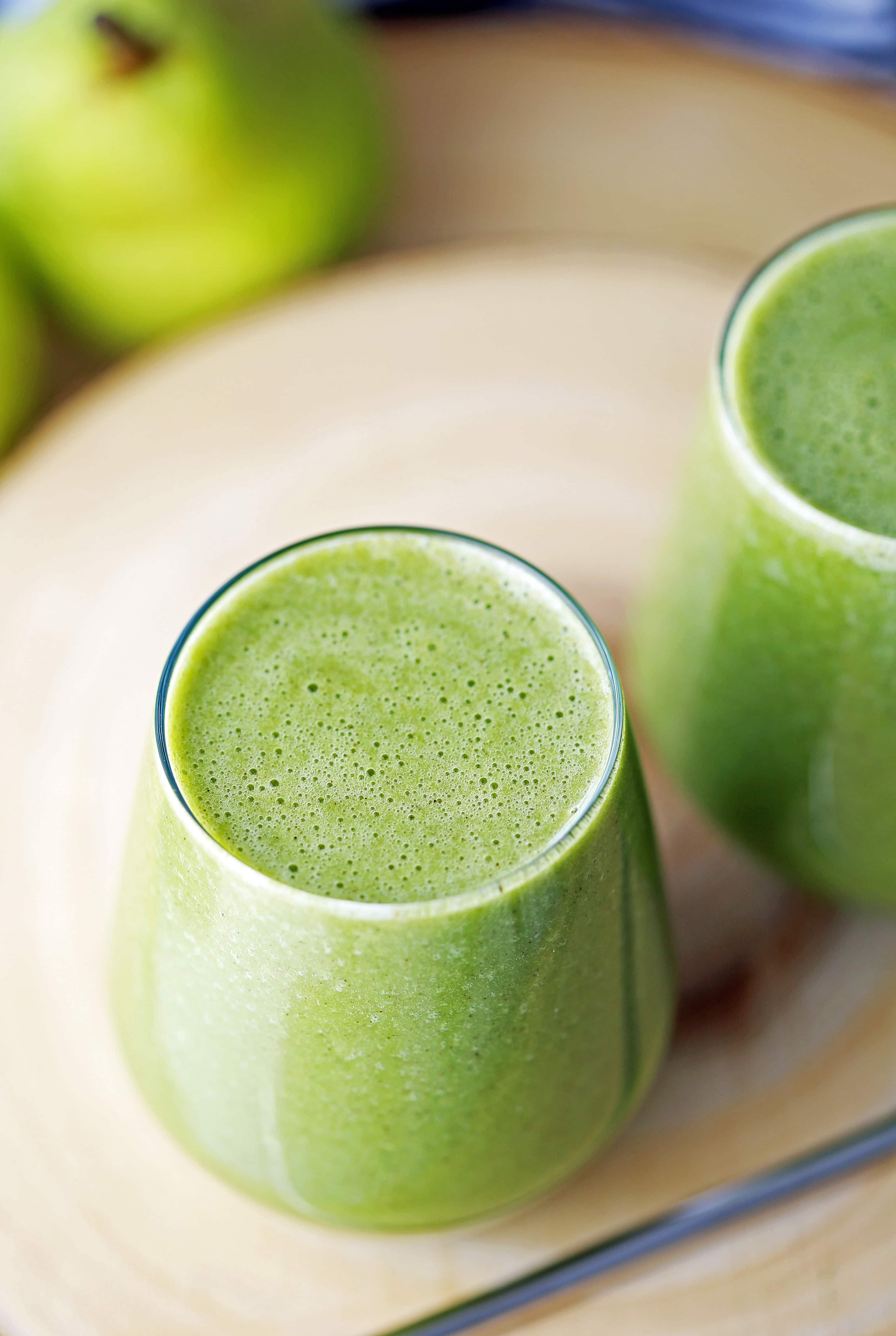 A close-up top view of a full glass of green smoothie made with pears, spinach, ground cinnamon, and almond milk.