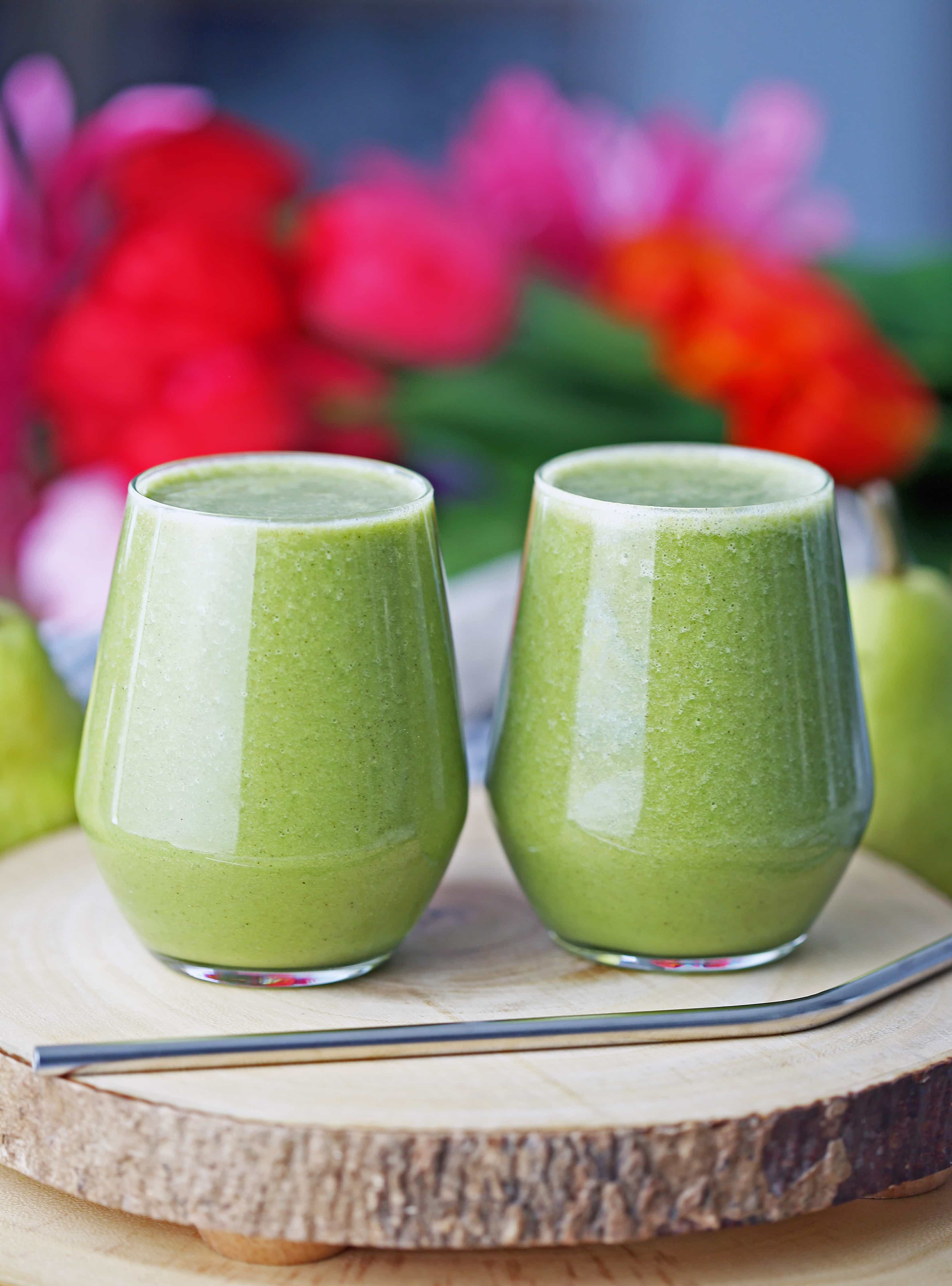 Cinnamon pear green smoothie in two glasses side by side on a wooden board.