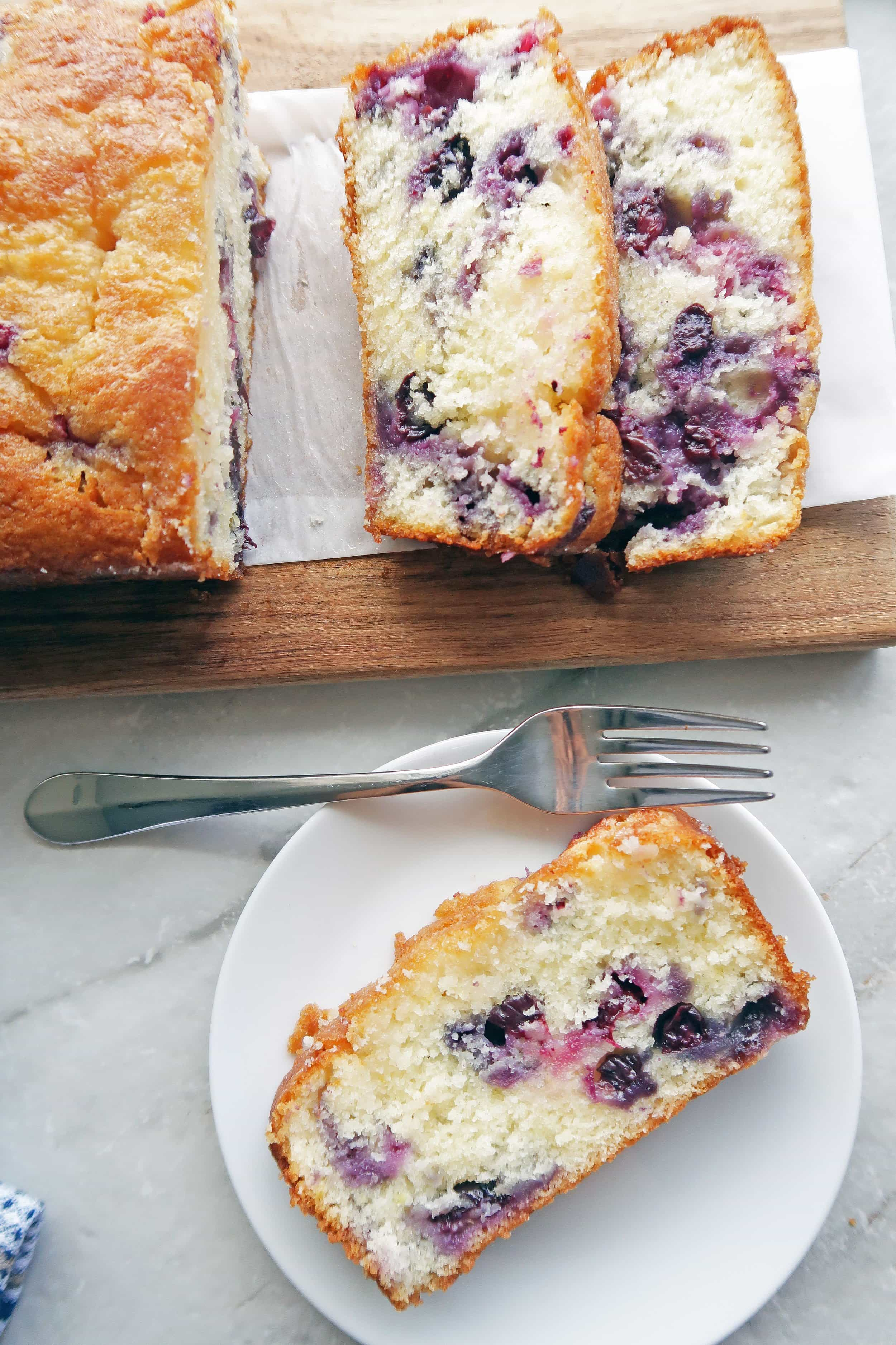 A slice of fluffy Classic Lemon Blueberry Loaf Cake on a white plate; the remaining sliced loaf cake on a long wooden board beside it.