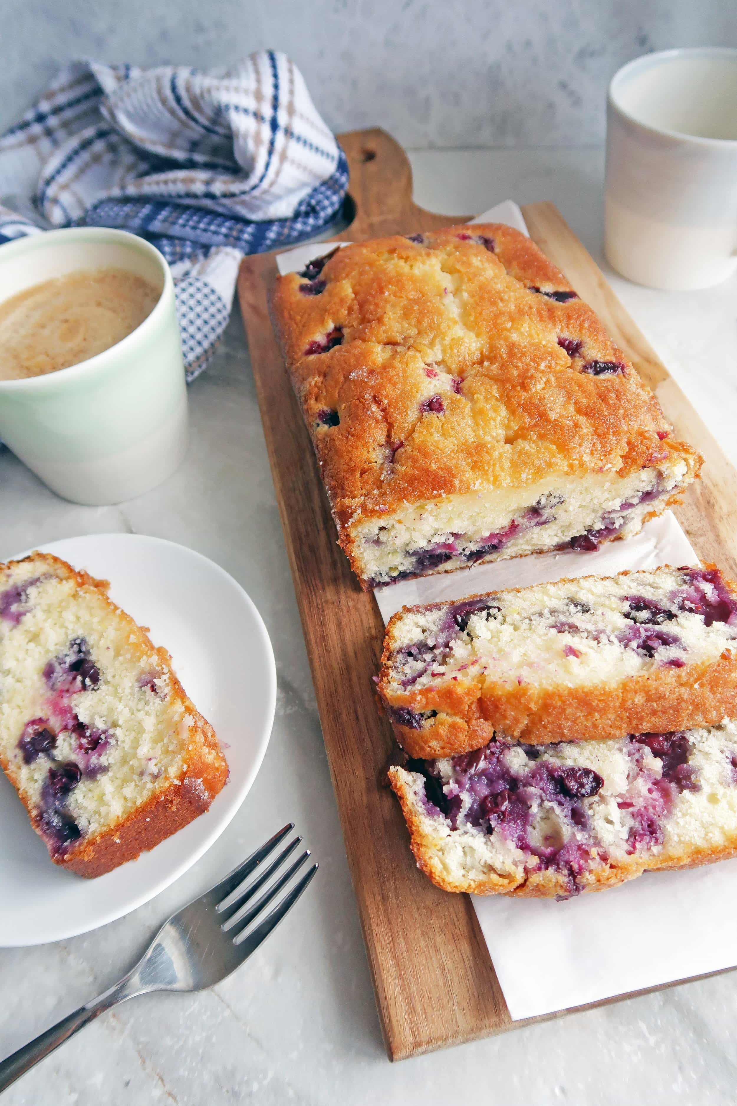A slice of fluffy Classic Lemon Blueberry Loaf Cake on a white plate; the remaining loaf cake on a long wooden board.