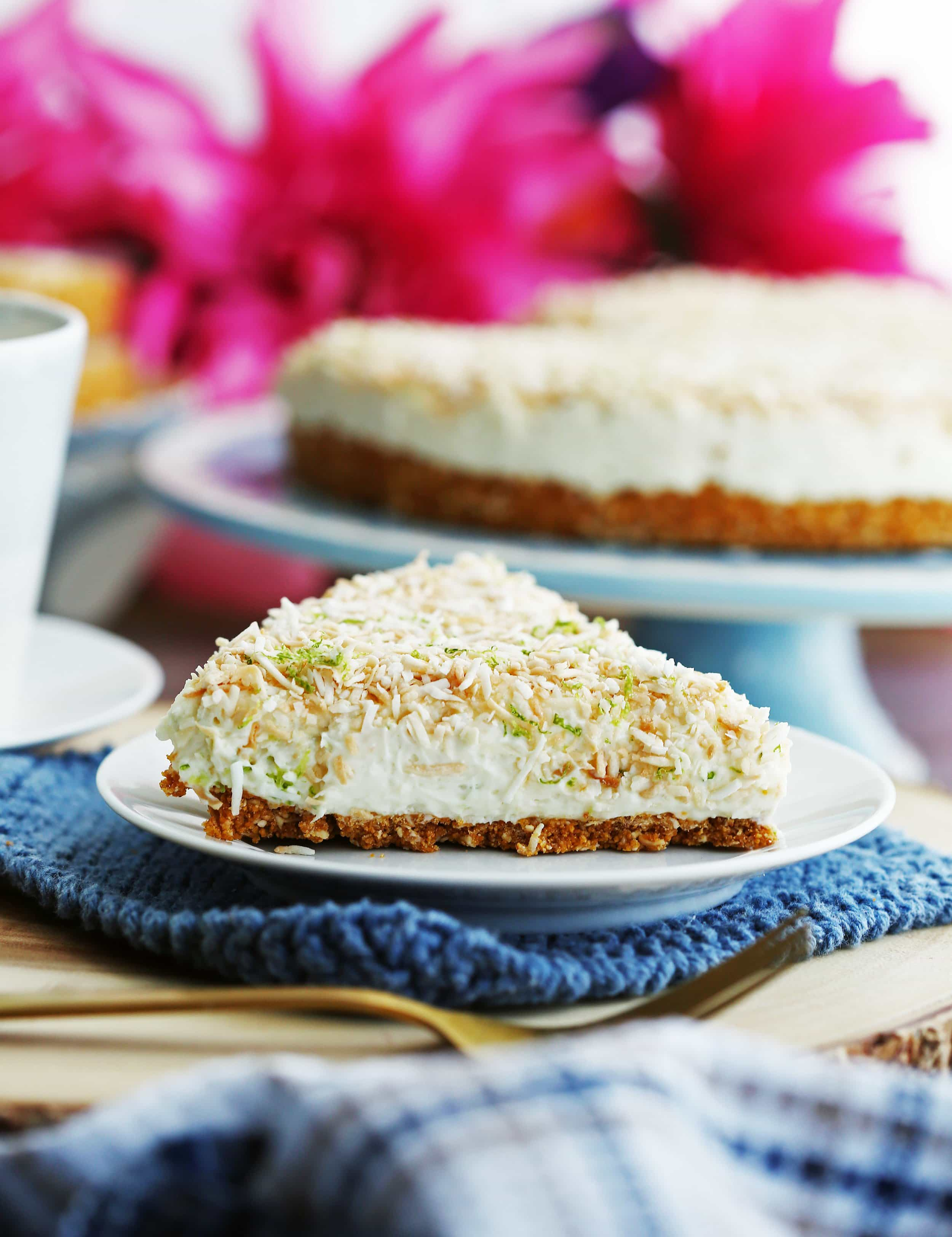 A closeup side view of a slice of no-bake coconut lime mascarpone cheesecake on a white plate.