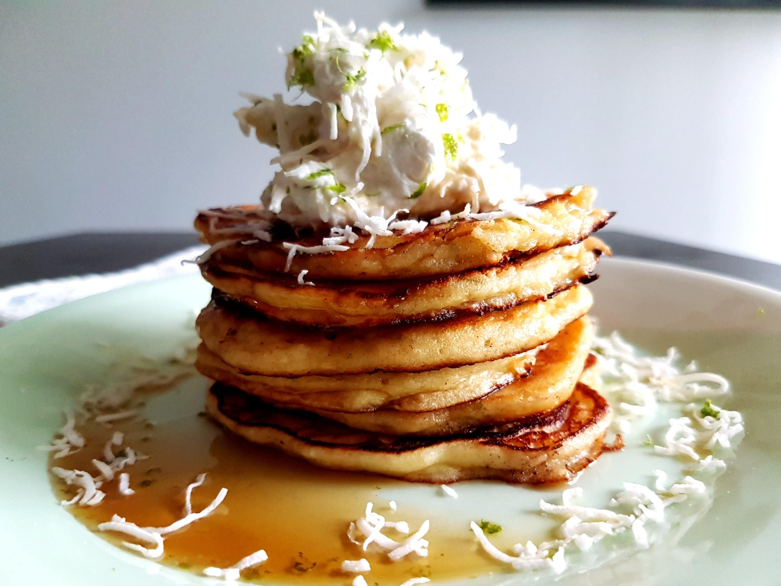 A stack of ricotta pancakes topped with coconut and lime whipped cream.