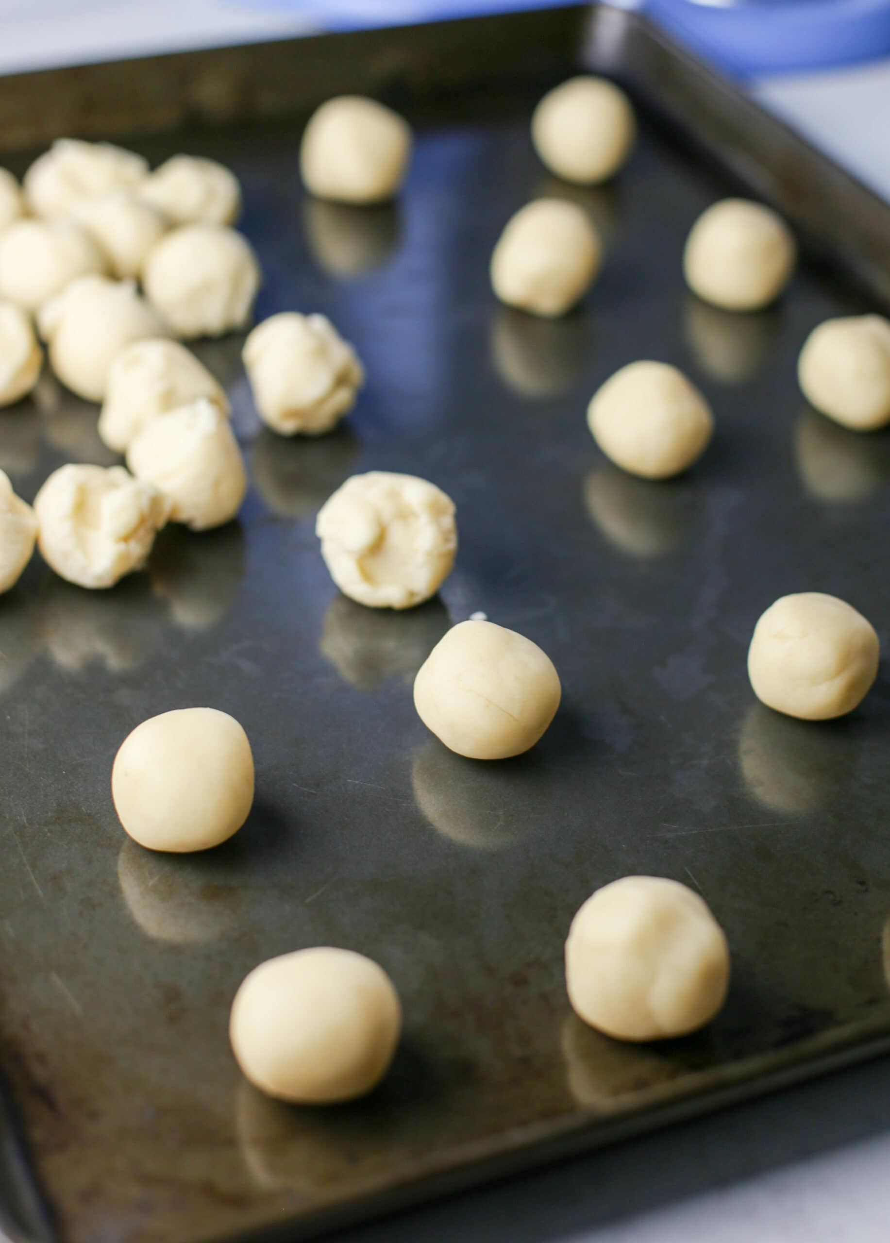 Raw condensed milk cookie dough balls on a baking sheet.