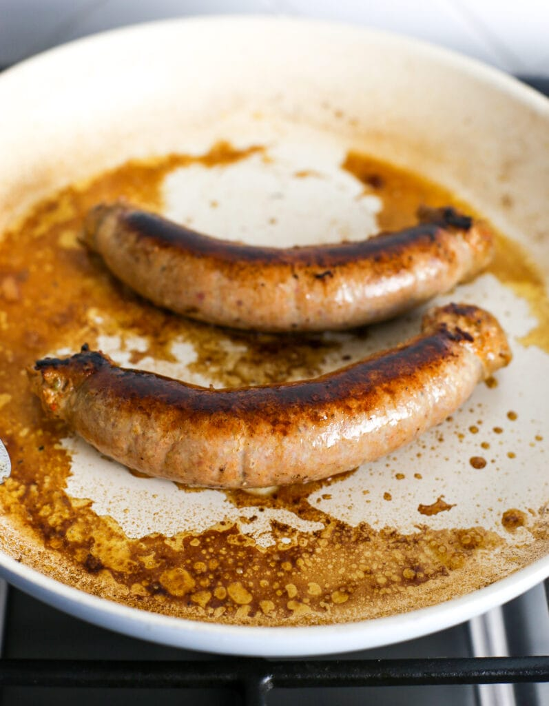 Two browned and cooked hot Italian sausages in a white frying pan.