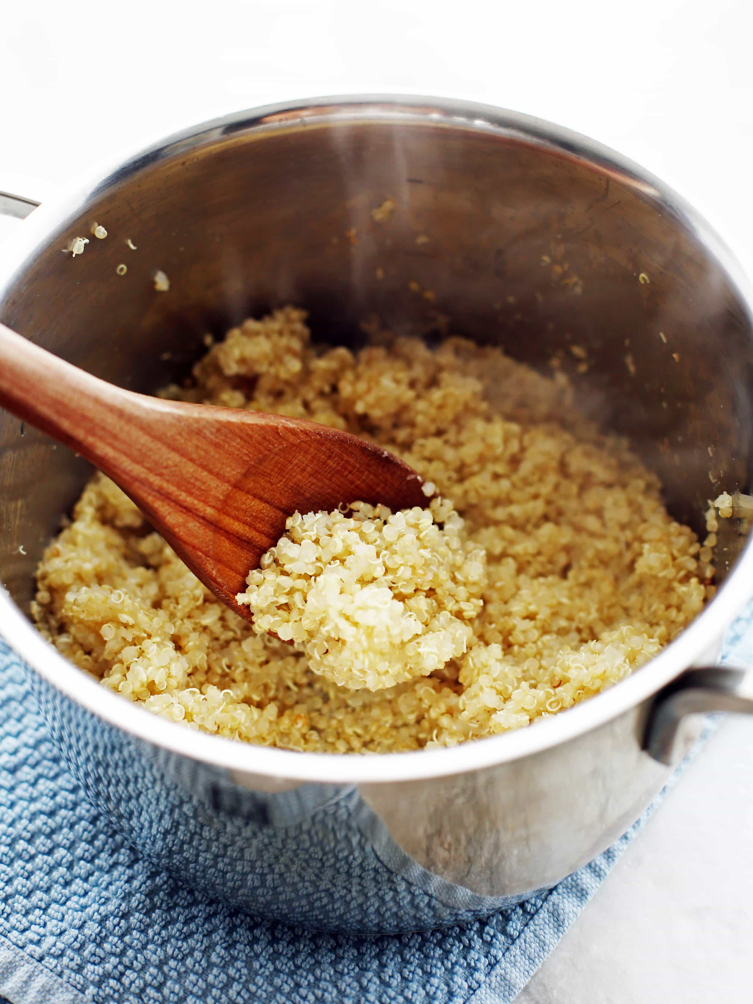 Cooked white quinoa in a small pot with a wooden spoon.
