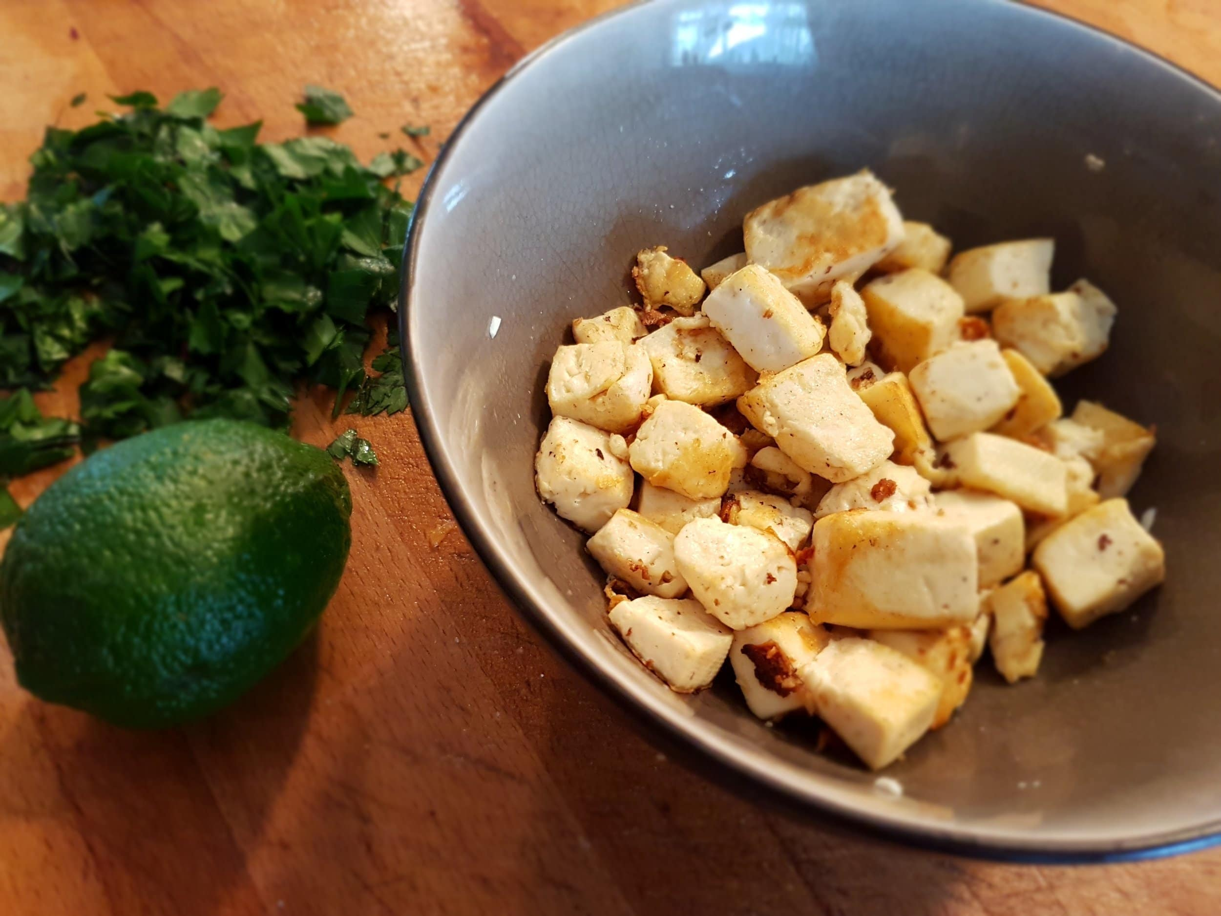Cooked tofu in a bowl with parsley and lime on the side.