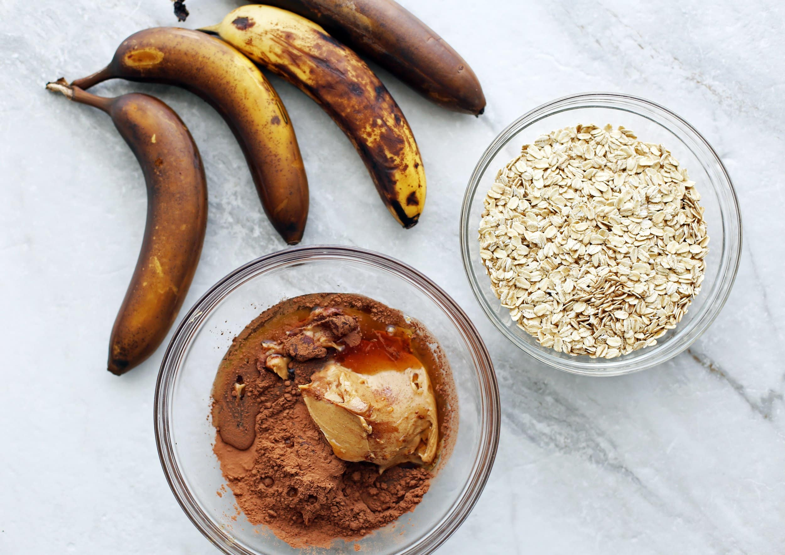 Four ripe banana, a bowl of peanut butter, cocoa powder, and maple syrup, and another bowl with oats.