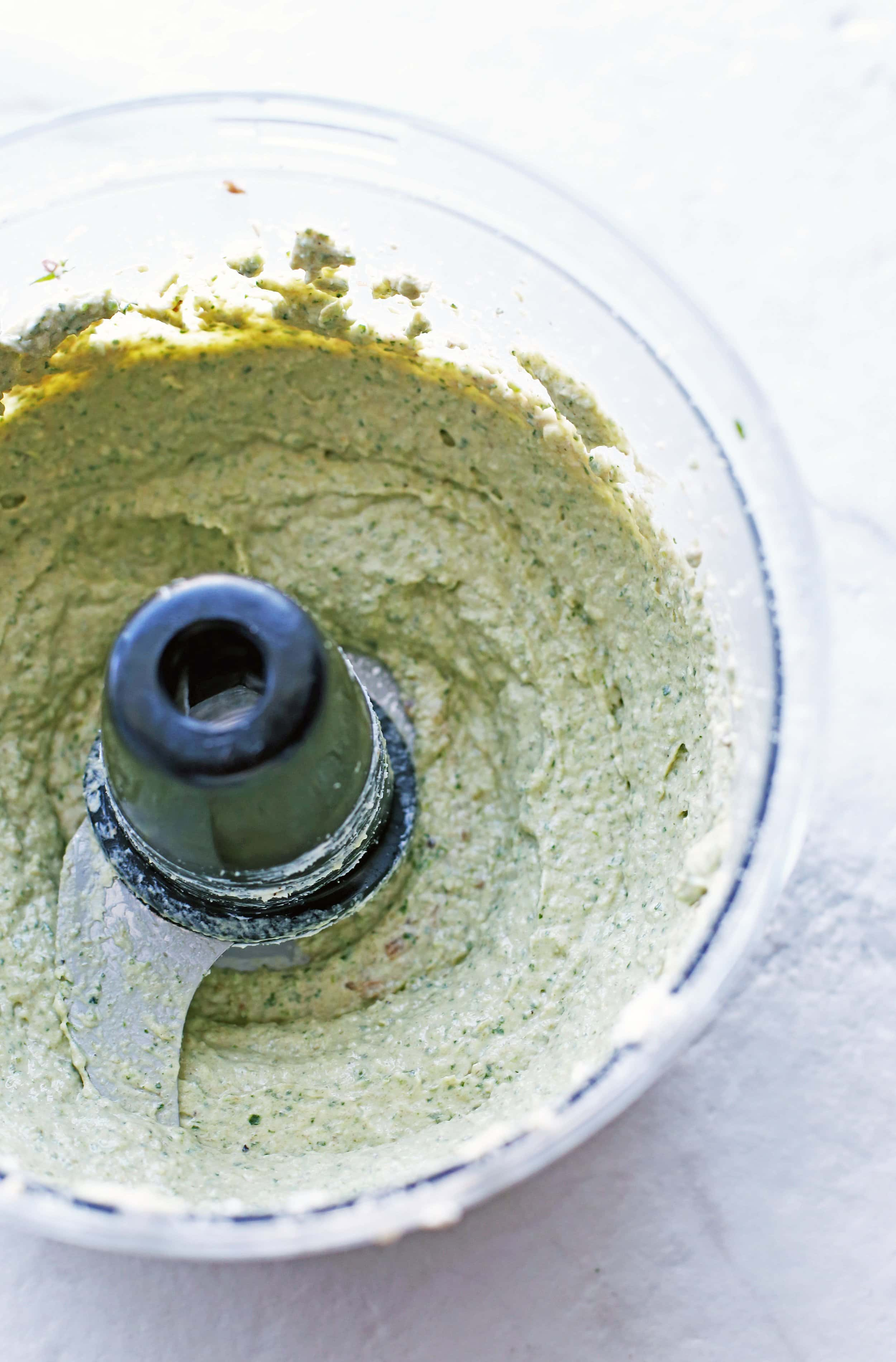 A creamy cream cheese mixture in a food processor.