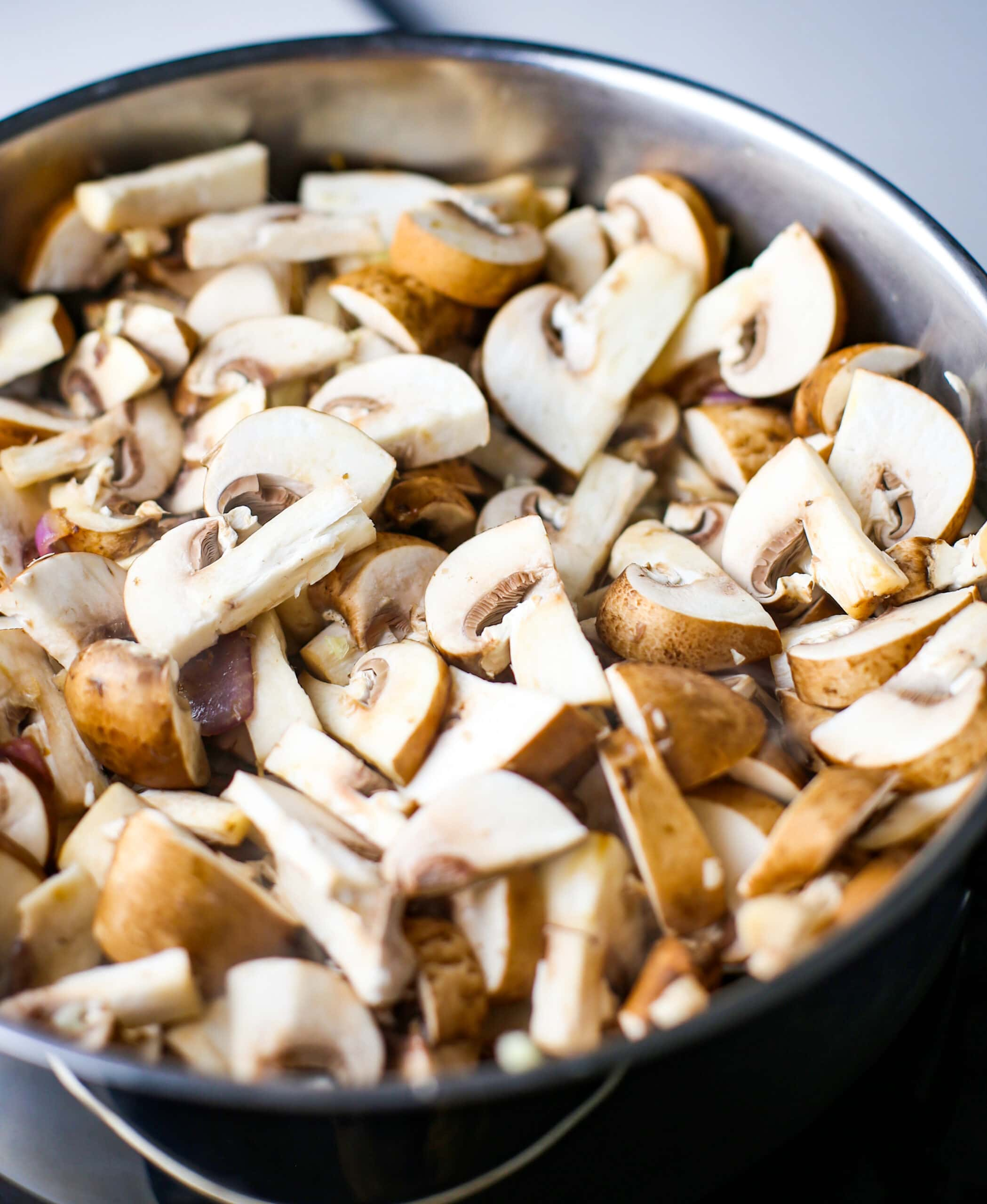 Sliced cremini mushrooms in a stainless steel saucepan.
