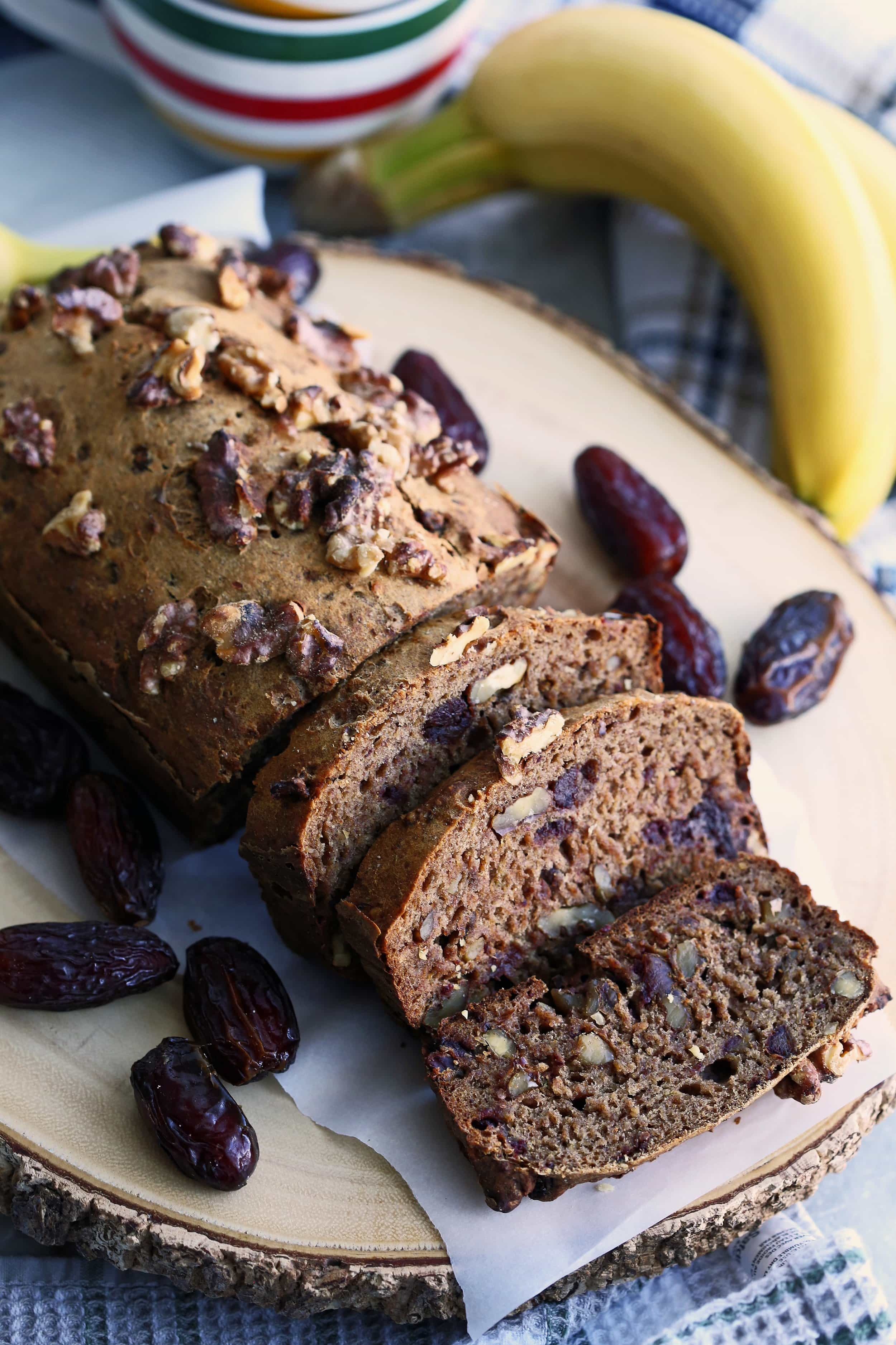 Sliced Date Banana Nut Bread surrounded by Medjool dates on a round wooden platter.