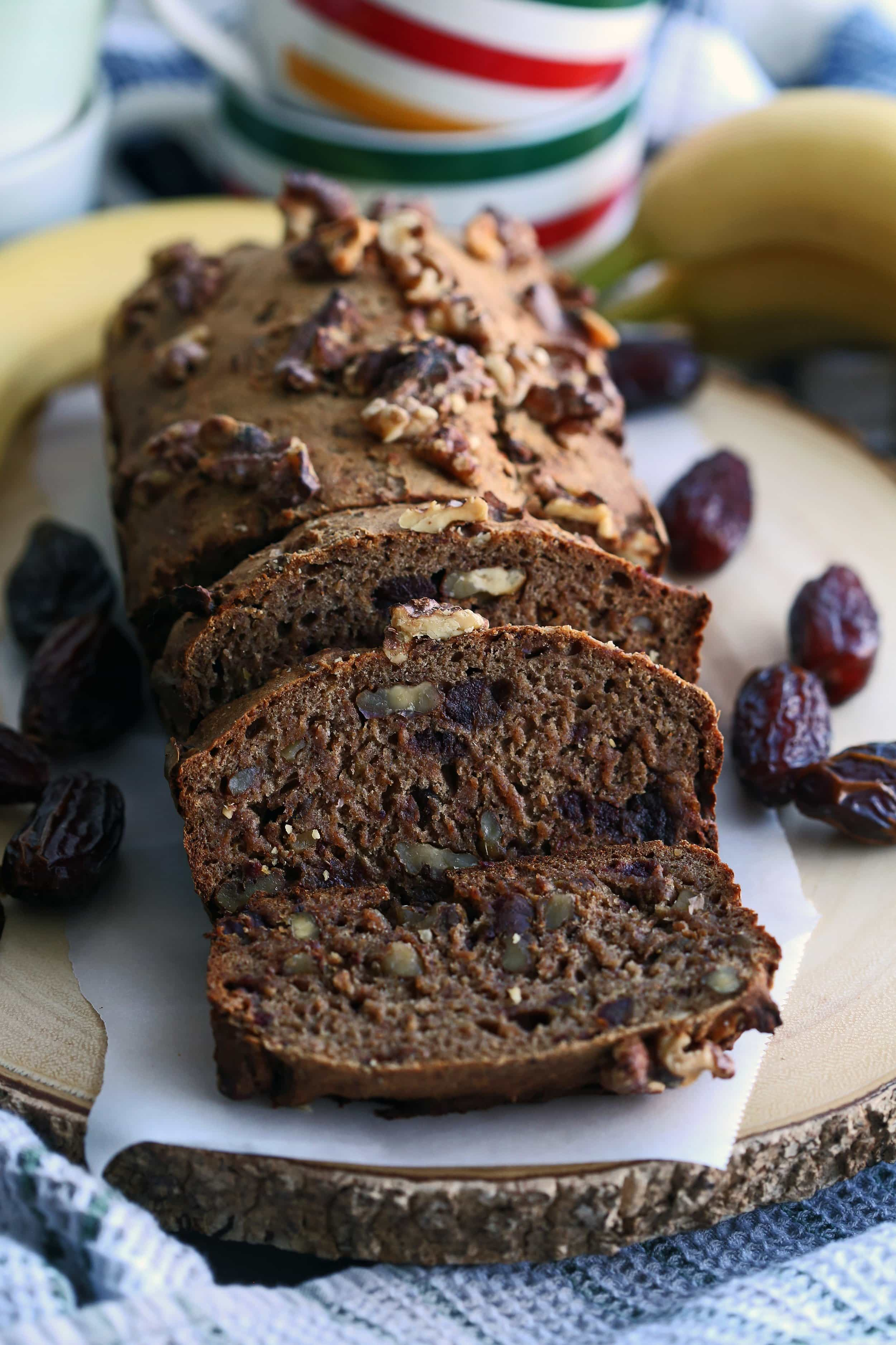 A loaf of banana bread with Medjool dates and walnuts surrounded by fresh bananas and dates on a wooden platter.