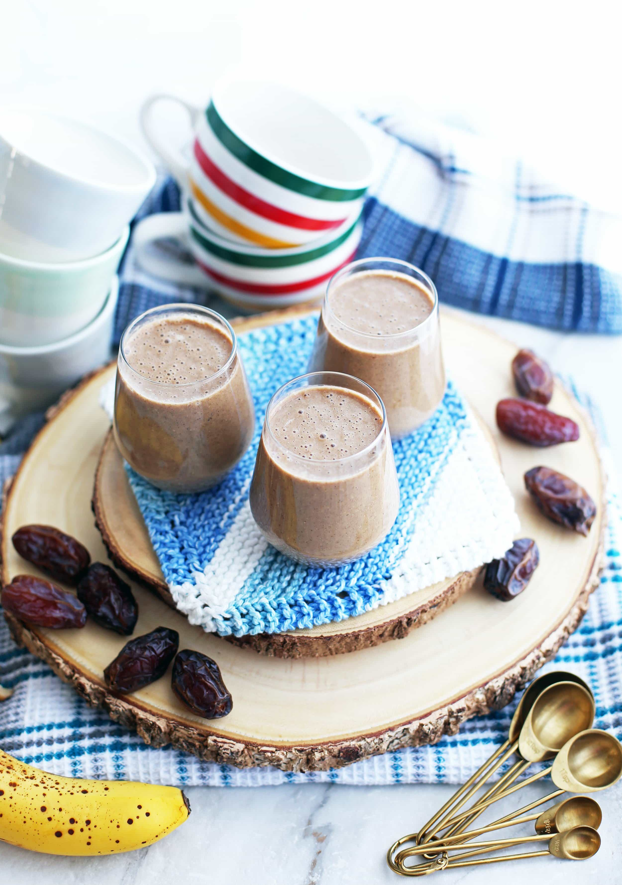 Three glasses of creamy date coffee breakfast smoothies on a wooden platter surrounded by medjool dates, measuring spoons, and coffee mugs.