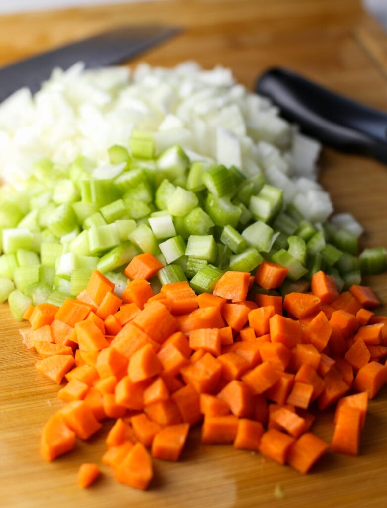 Diced carrots, onions, and celery on a cutting board.