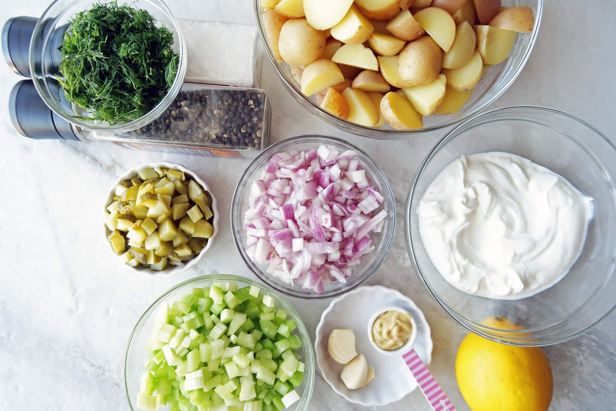 Separate bowls of potatoes, dill, onions,celery, red onions, and Greek yogurt.