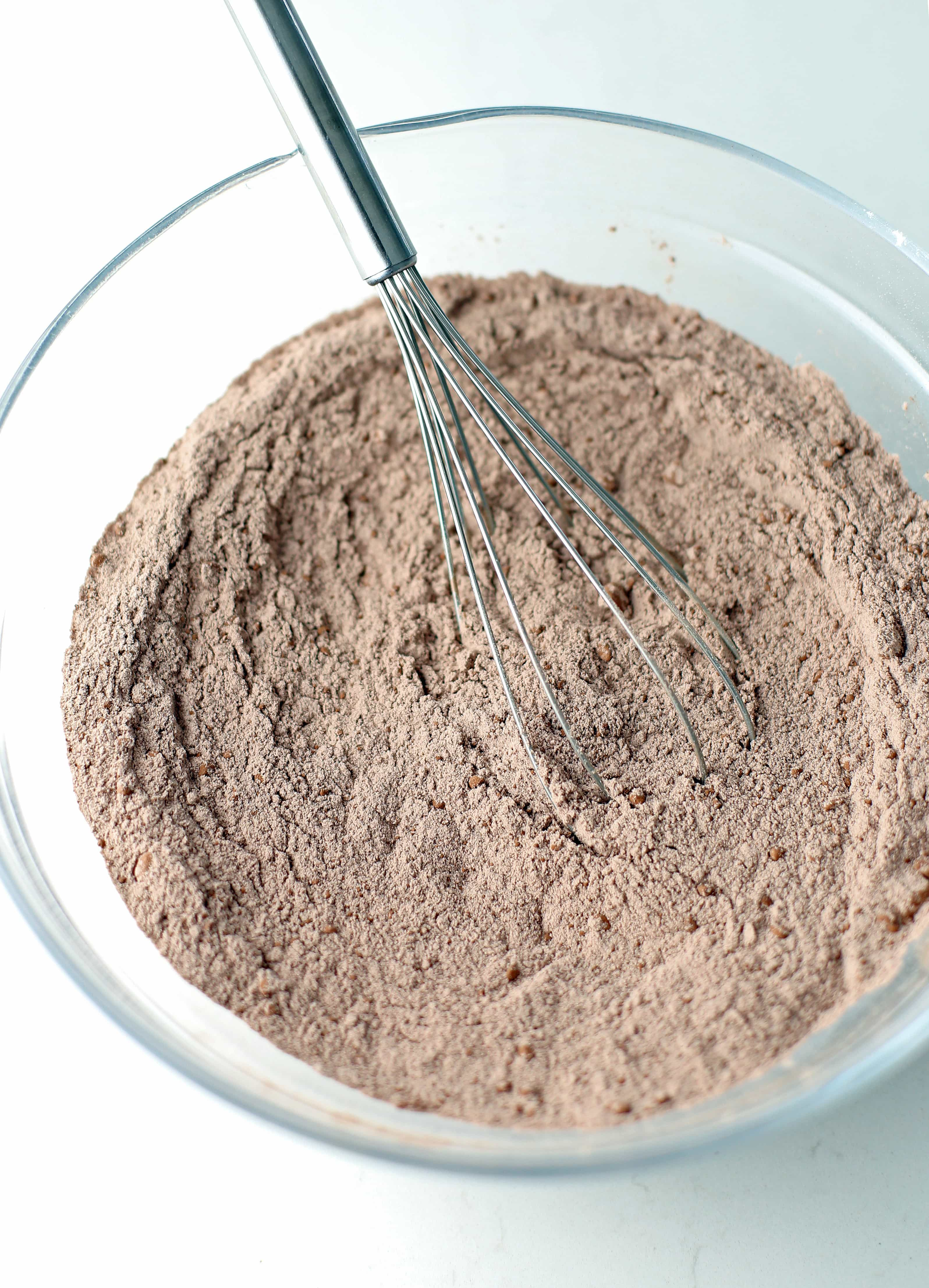 Dry baking ingredients including cocoa power and all-purpose flour mixed in a glass bowl.