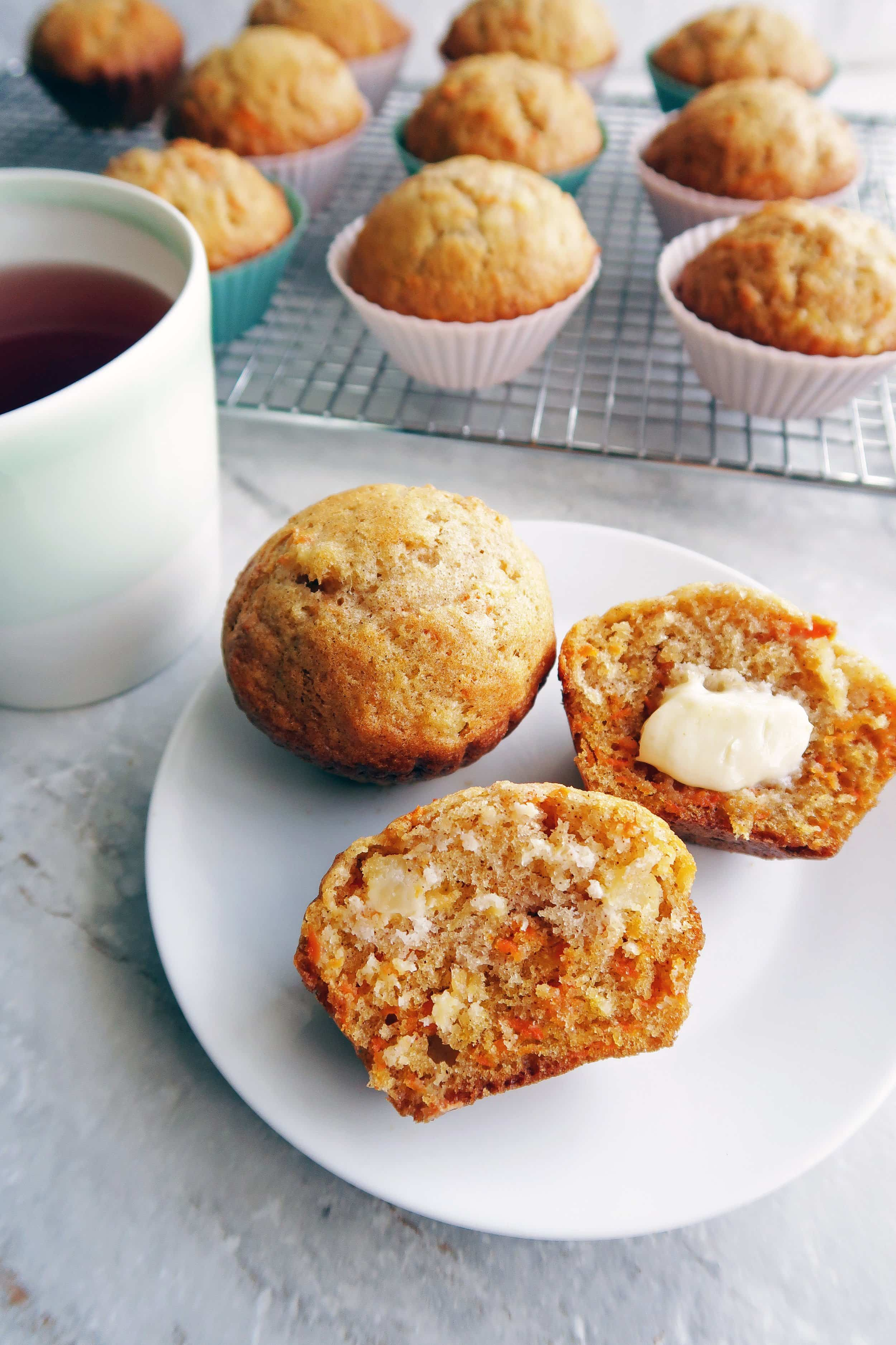 Two Carrot Pineapple Muffin, one cut in half with butter, on a white plate with more muffins on a cooling rack in the background.