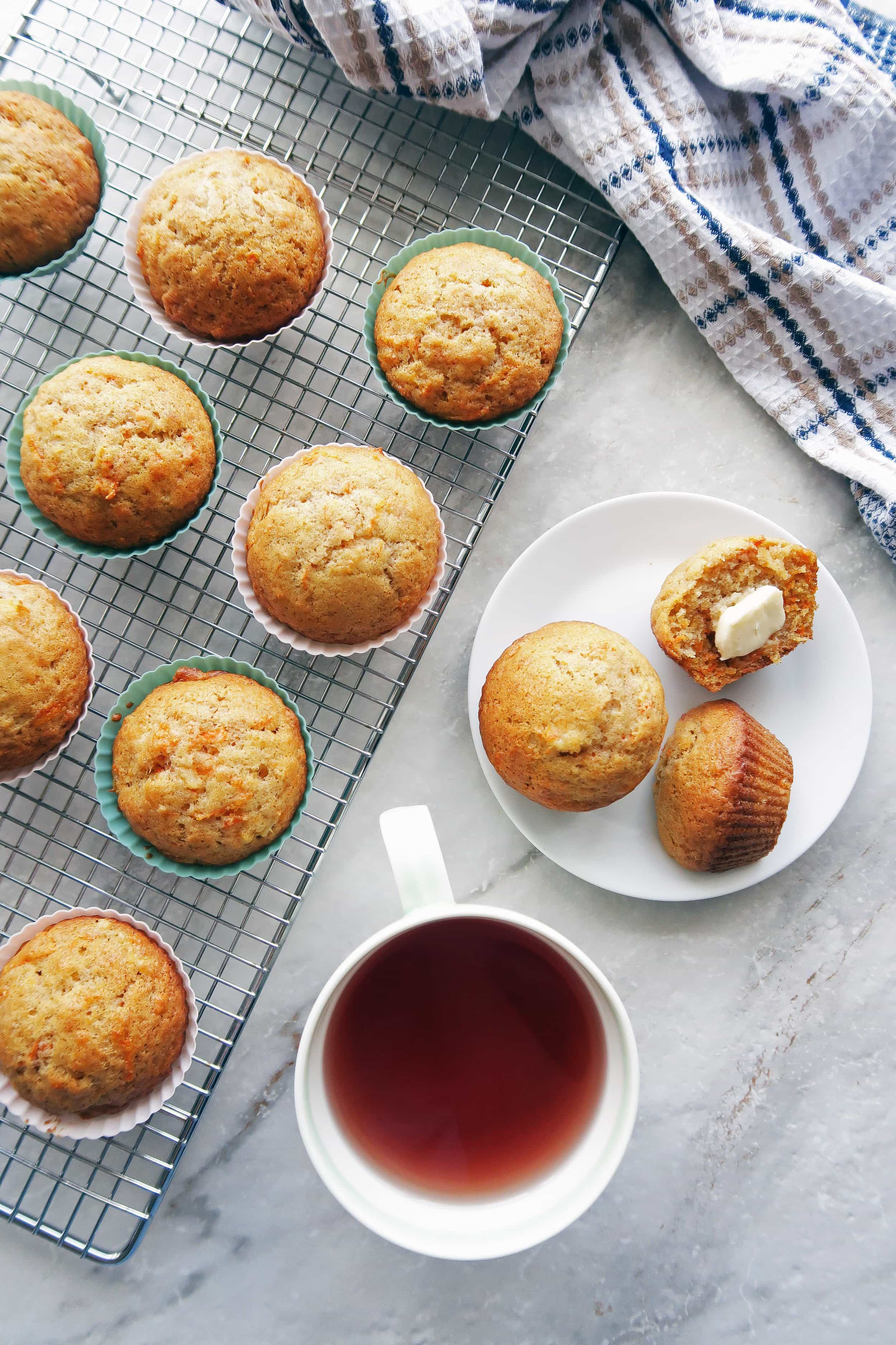 Overhead view of two carrot Pineapple Muffins on small white plate, muffins on a cooling rack, and a cup of tea.