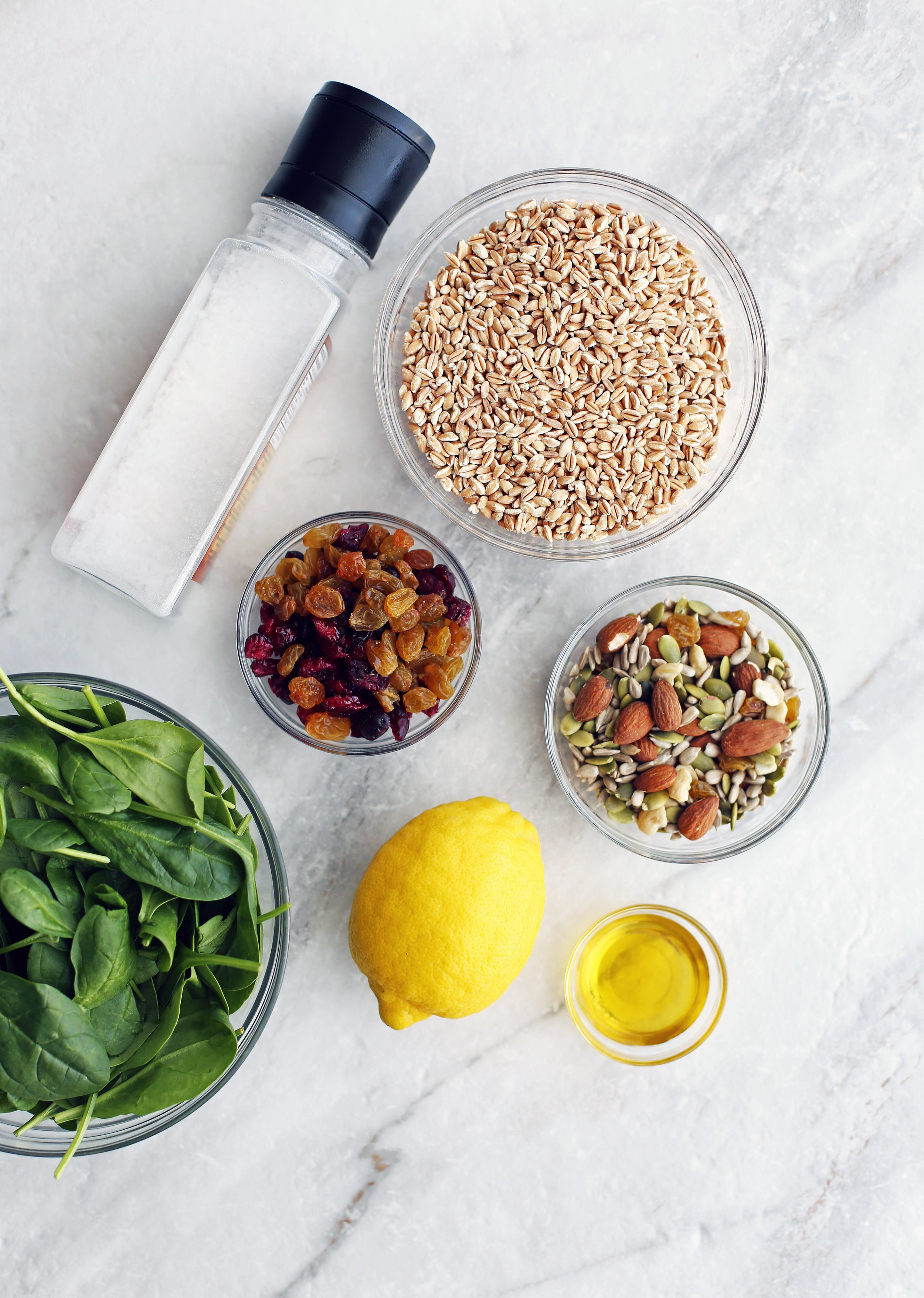 Bowls of baby spinach, dried fruit, nuts and seeds, farro, olive oil along with a lemon and a salt shaker.