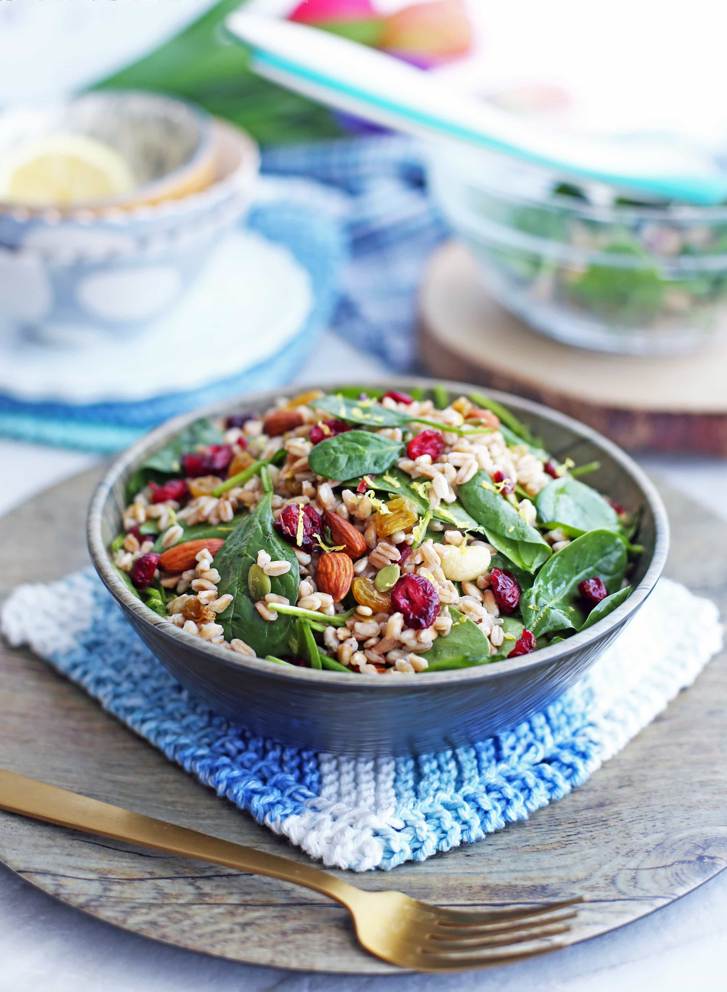 Farro and Spinach Salad with Dried Fruit and Nuts in a wooden bowl;fork in front of the bowl.