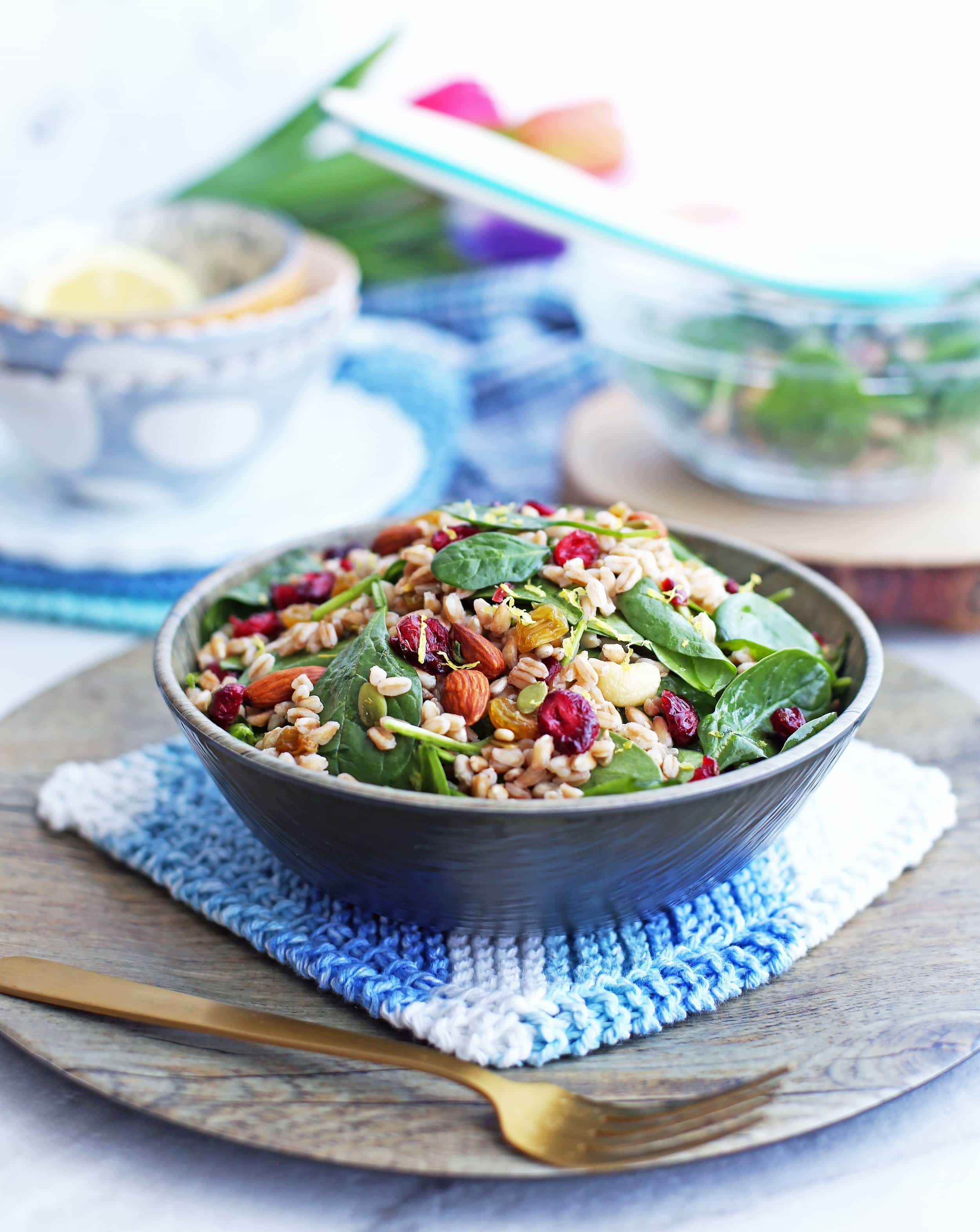 Farro and Spinach Salad with Dried Fruit and Nuts in a wooden bowl with a fork to its side; more salad behind it.