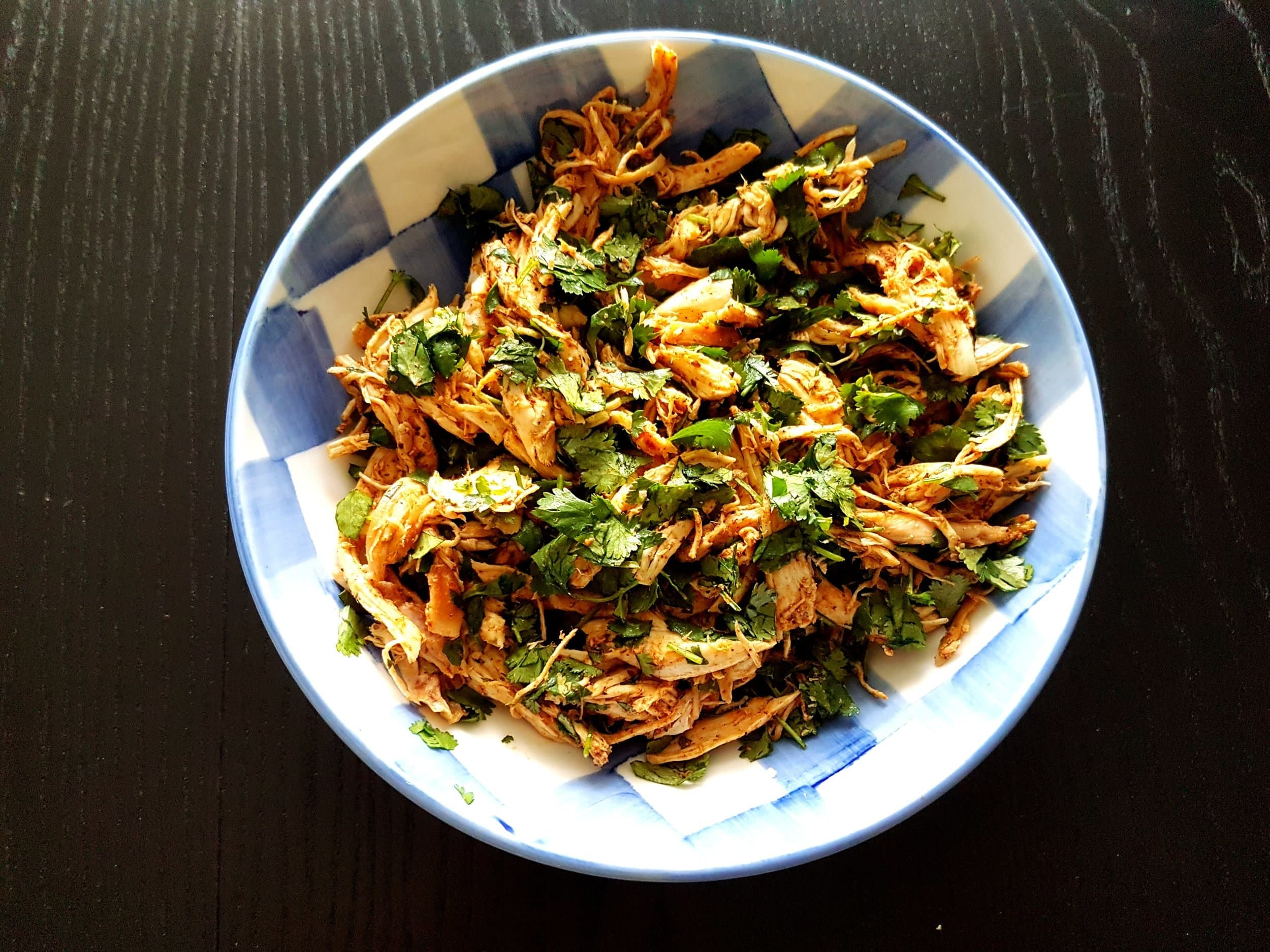 Shredded chicken in a bowl mixed with fresh chopped cilantro.
