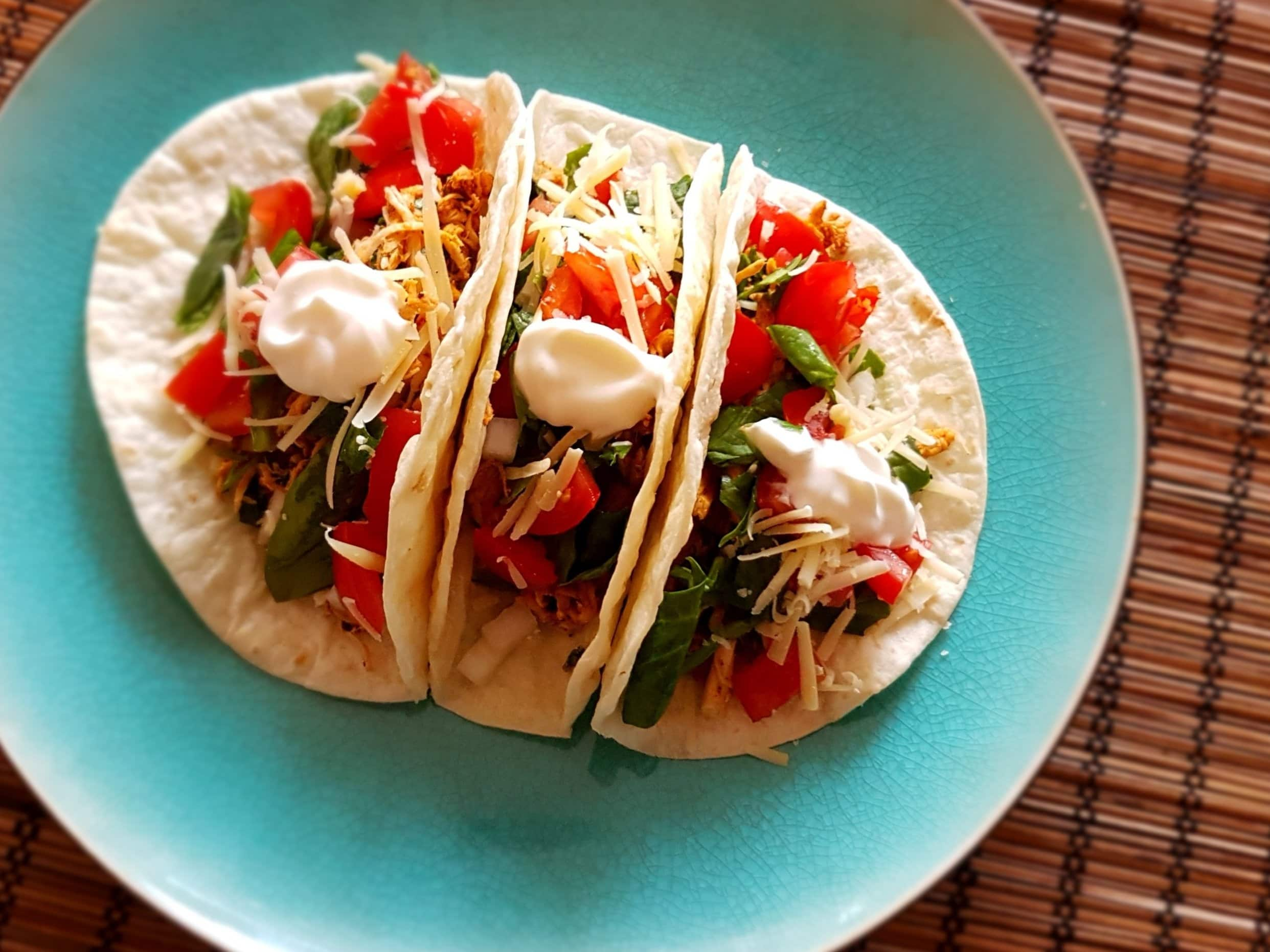 Three chicken taco on a plate.