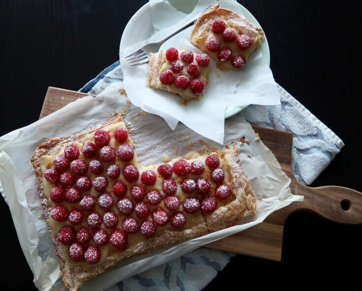 """<span style=""""font-size:16px"""">Flaky, buttery puff pastry is topped with freshly made lemon curd, sweet raspberries, and dusted with confectioner's sugar and lemon zest.</span>"""