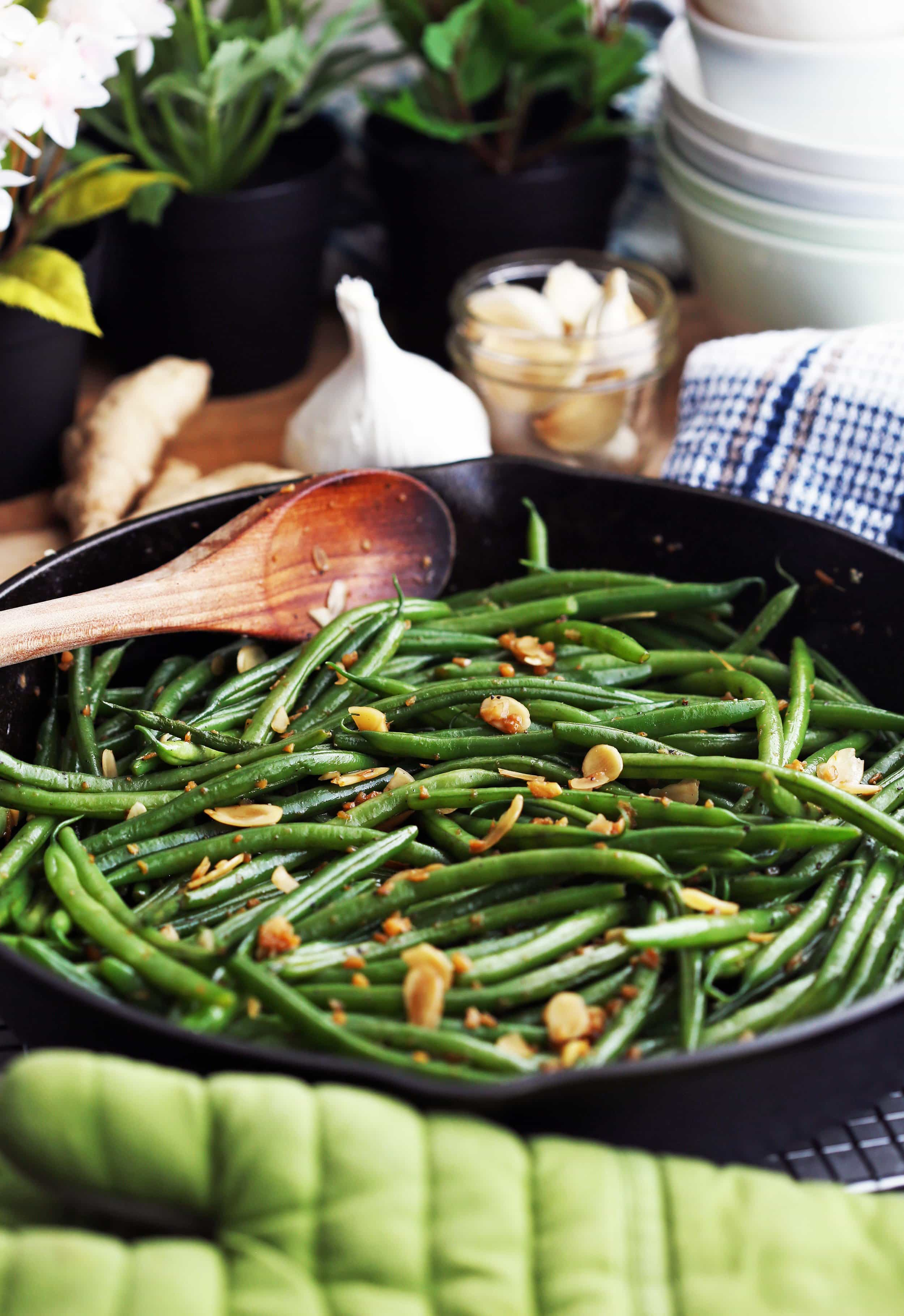 Sautéed green beans with ginger, garlic, and almonds in an large cast iron skillet.